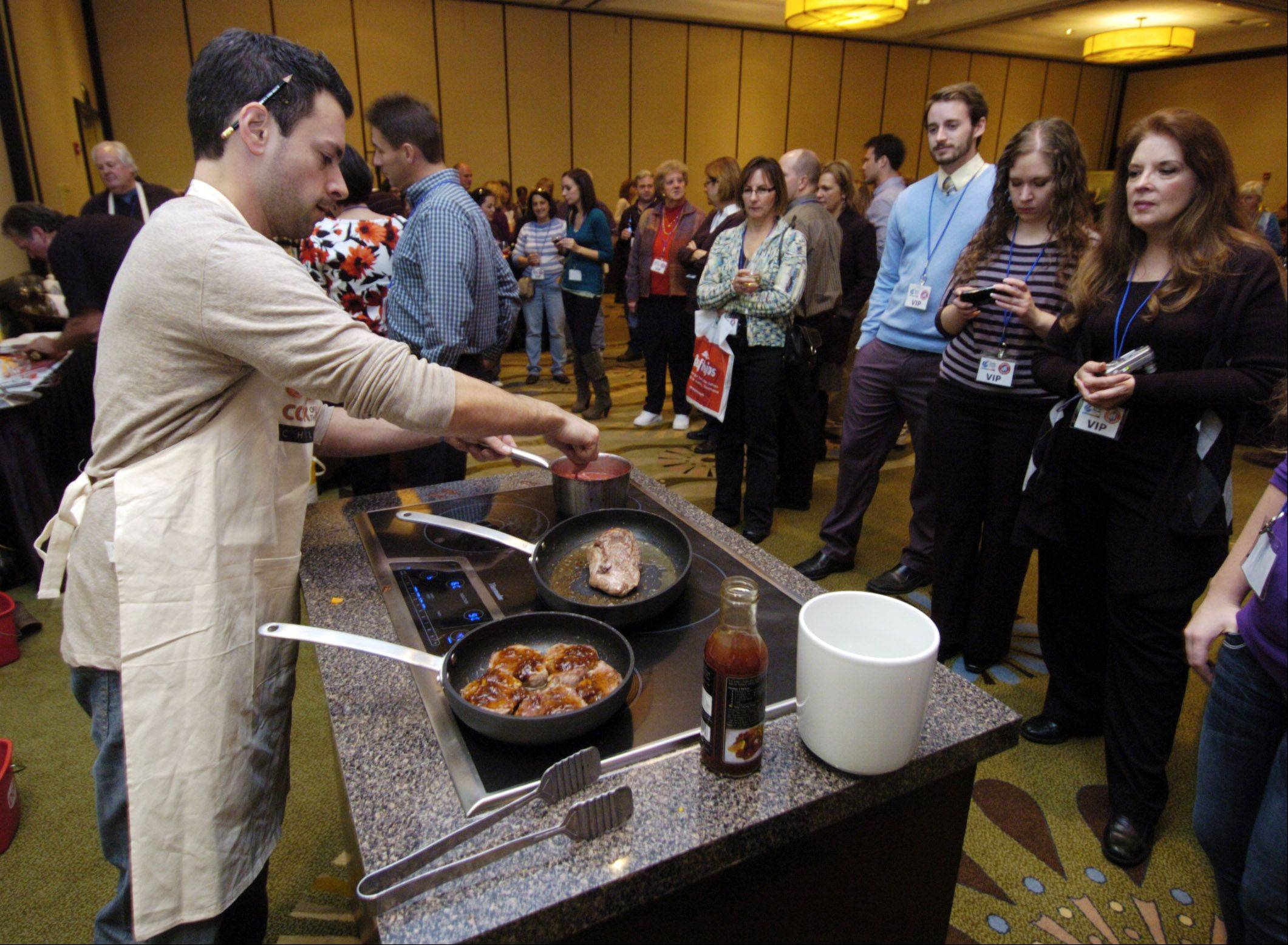 A crowd gathers to watch contestant Michael Lalagos, of Schaumburg, as he competed in the 2011 Daily Herald Cook of the Week Challenge cook-off. Tickets are now on sale for the 2012 cook-off.