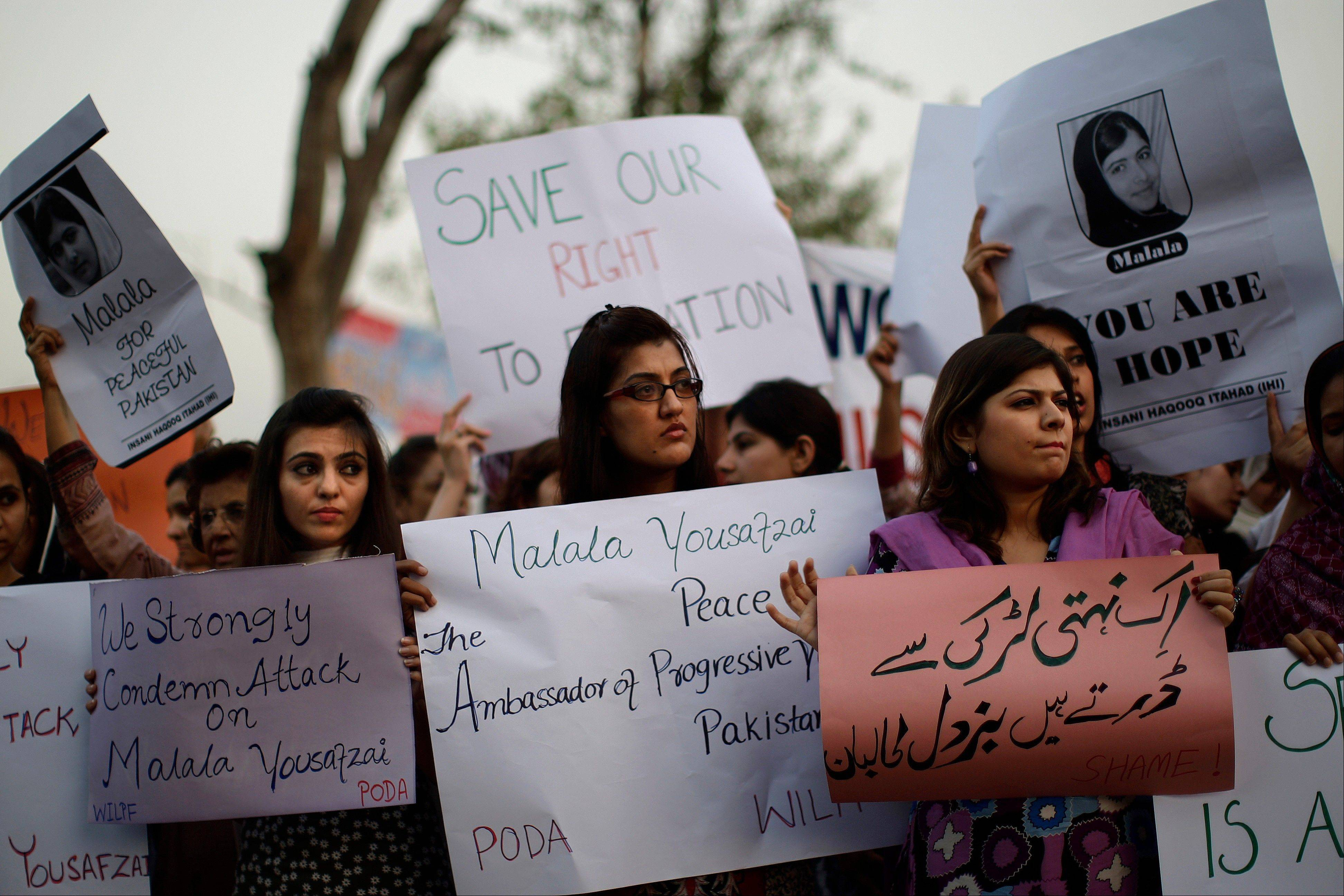 "Pakistani women hold banners Wednesday during a protest condemning the attack on schoolgirl Malala Yousufzai, in Islamabad, Pakistan. Pakistani doctors successfully removed a bullet Wednesday from the neck of a 14-year-old girl who was shot by the Taliban for speaking out in support of education for women, a government minister said. Banner bottom right reads, ""The Taliban is afraid of an unarmed girl."""