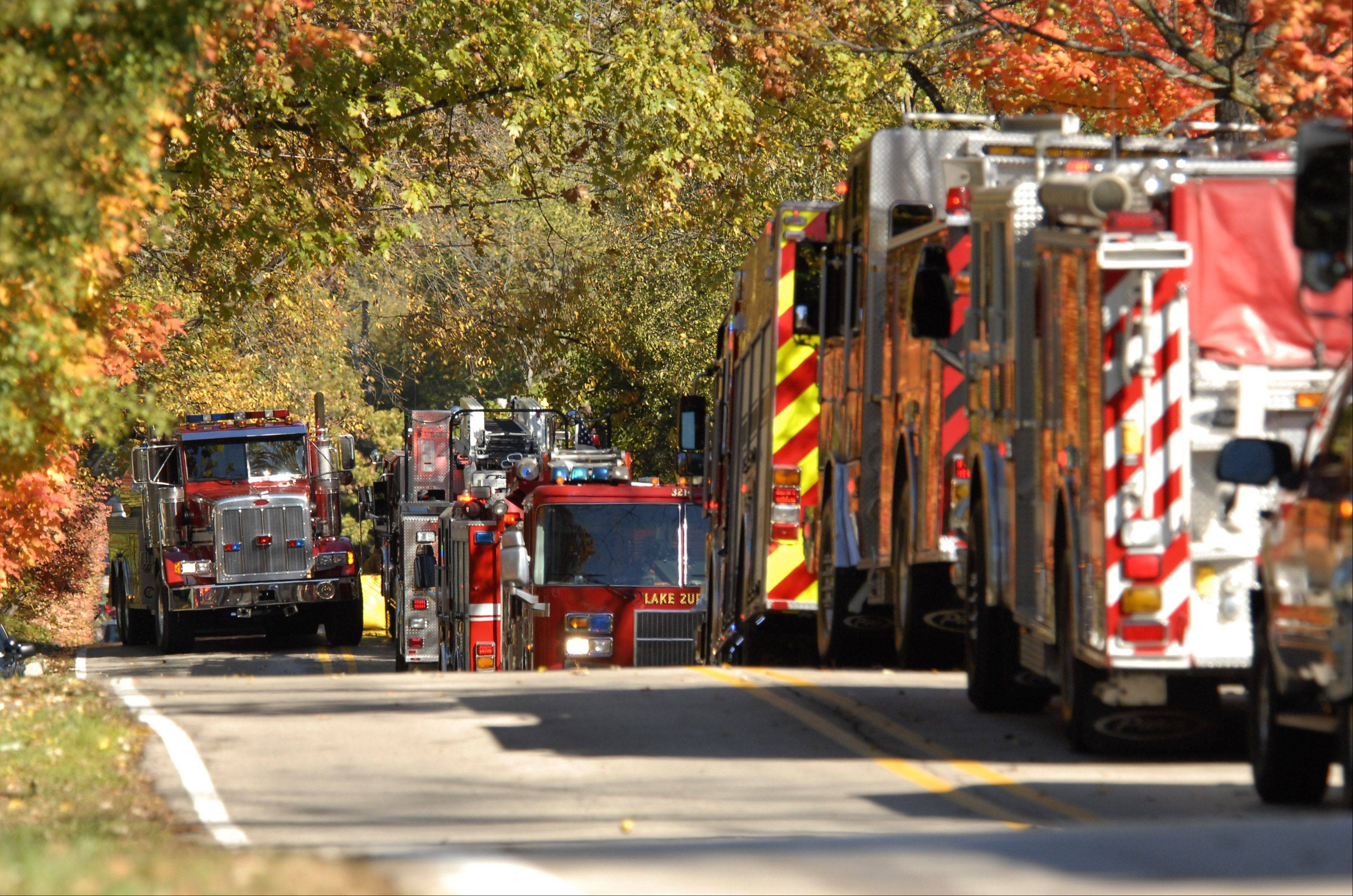 Fire trucks line Ridge Road just north of Spring Creek Road in Barrington Hills while responding to a four-alarm fire Wednesday morning.