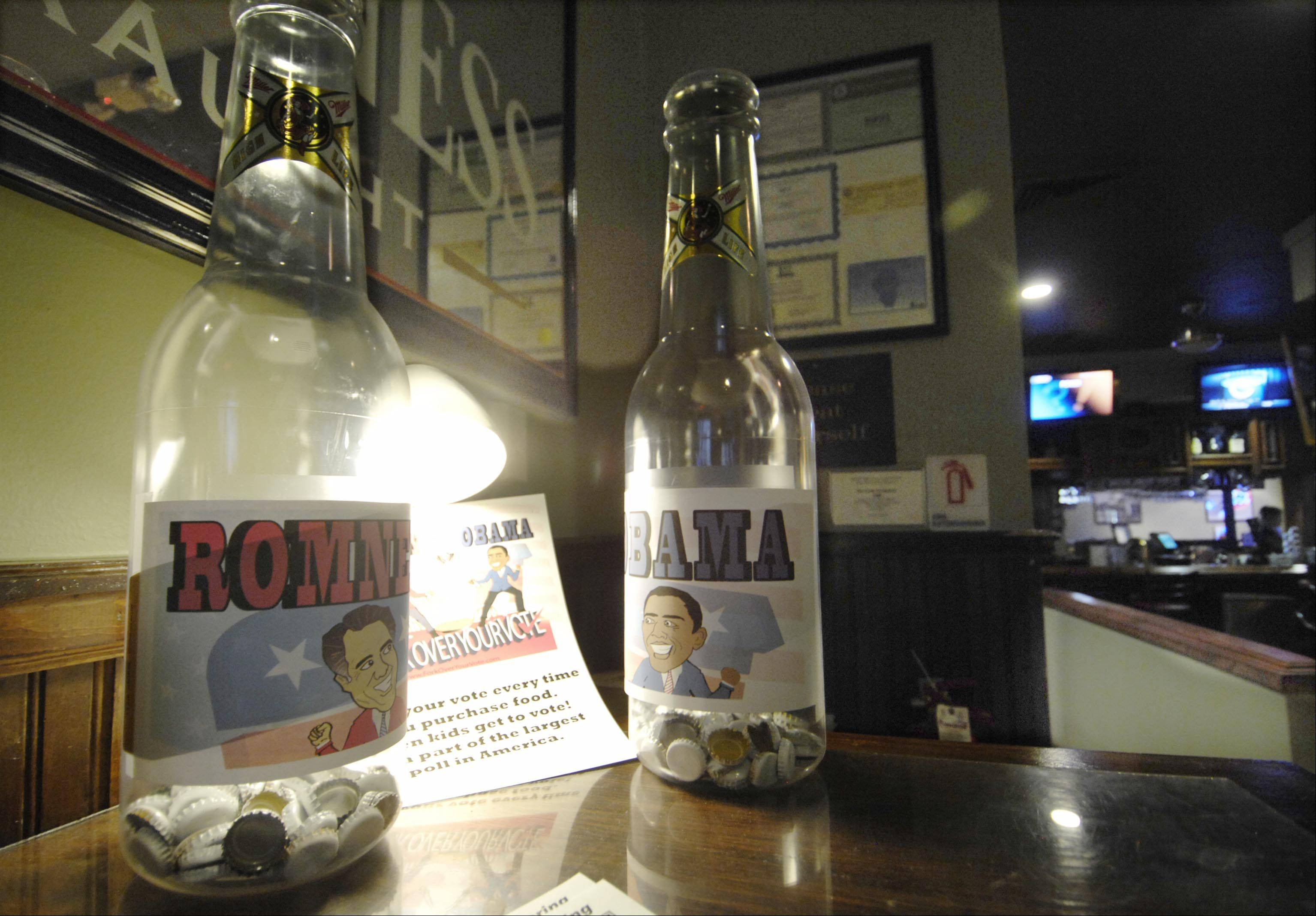 At Stanley's Ale House in South Elgin, patrons can drop a bottle cap into the oversized plastic bottle to vote for their presidential choice. Votes will be tallied with others across the country until Nov. 4.