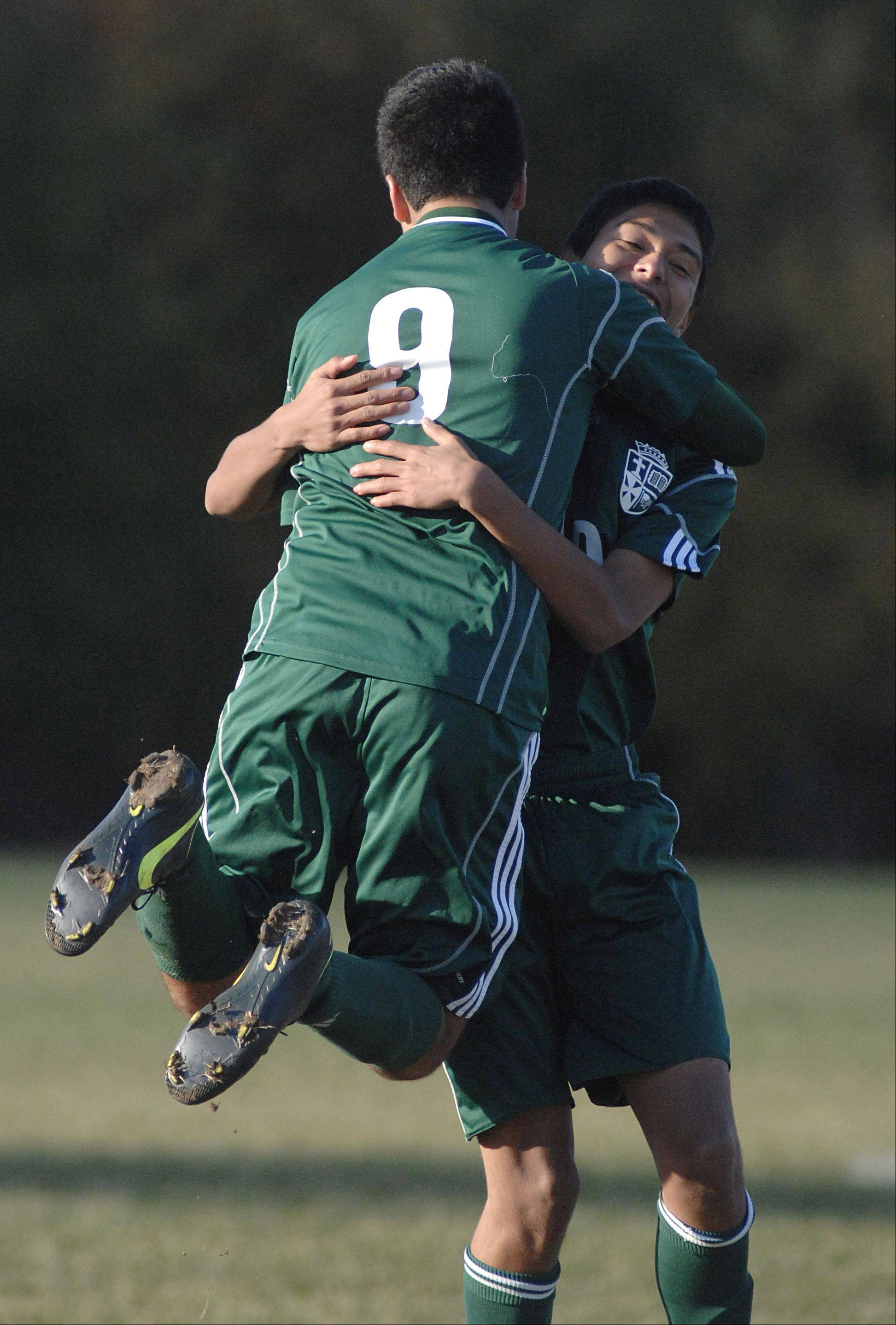 St. Edward's Alex Semler leaps into the arms of teammate Efrain Franco after scoring a goal on Elgin Academy in the first half of a Class 1A Westminster Christian regional semifinal on Wednesday.