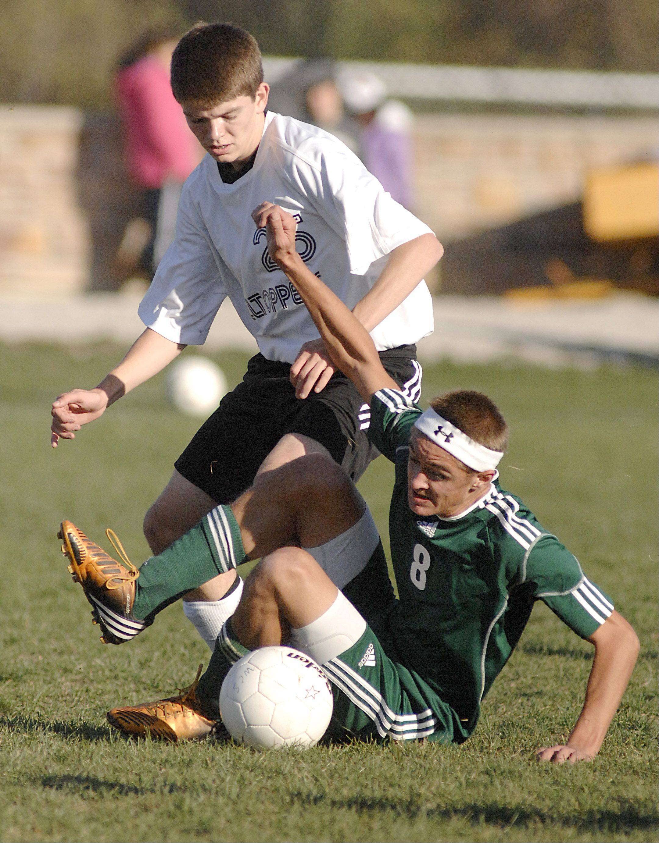 St. Edward's Johnny Shepherd tumbles as he and Elgin Academy's Billy Gracik battle for the ball in the first half on Wednesday.