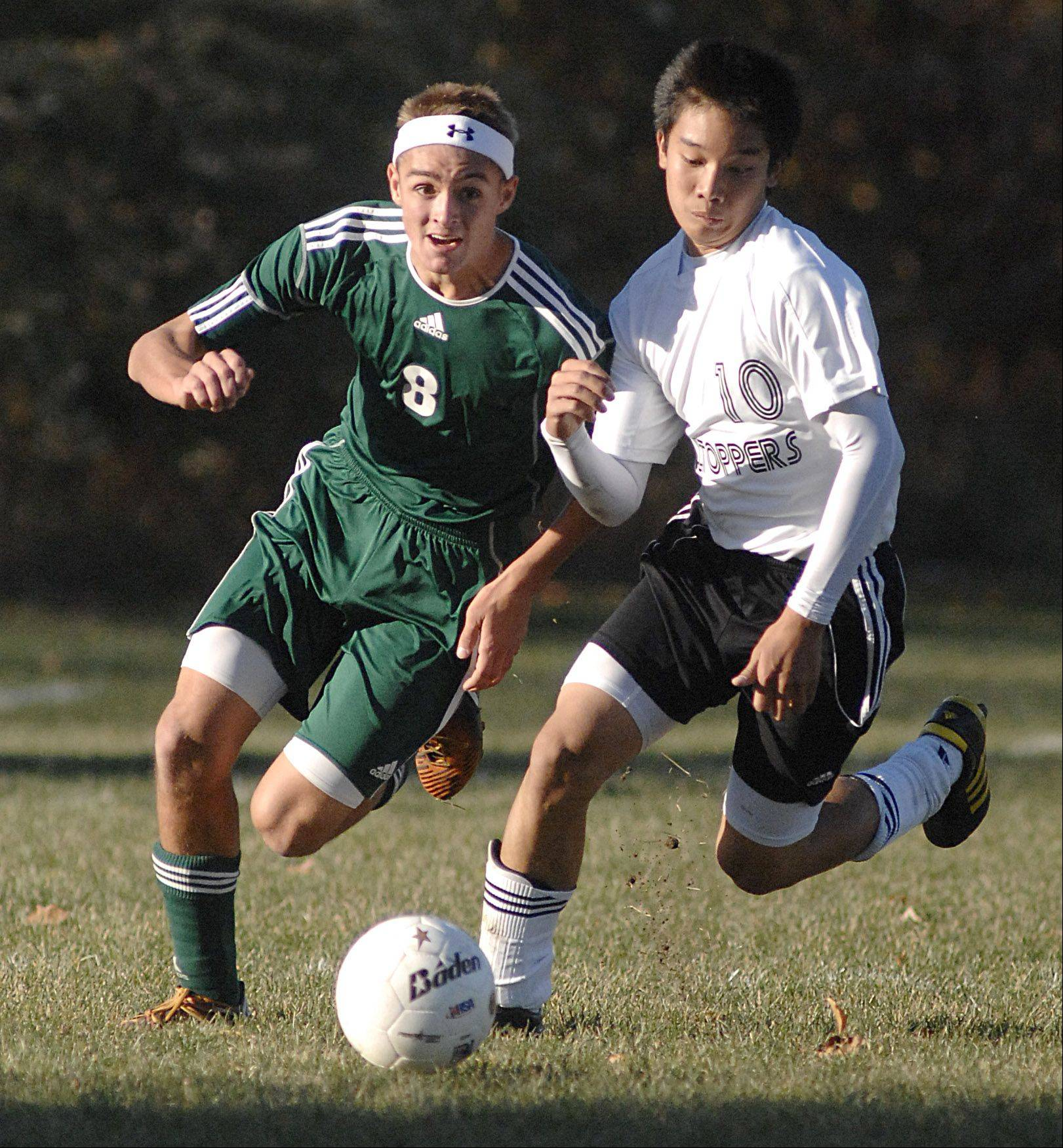 St. Edward's Johnny Shepherd and Elgin Academy's Tano Xayasarn fight for the ball in the first half on Wednesday, October 10.