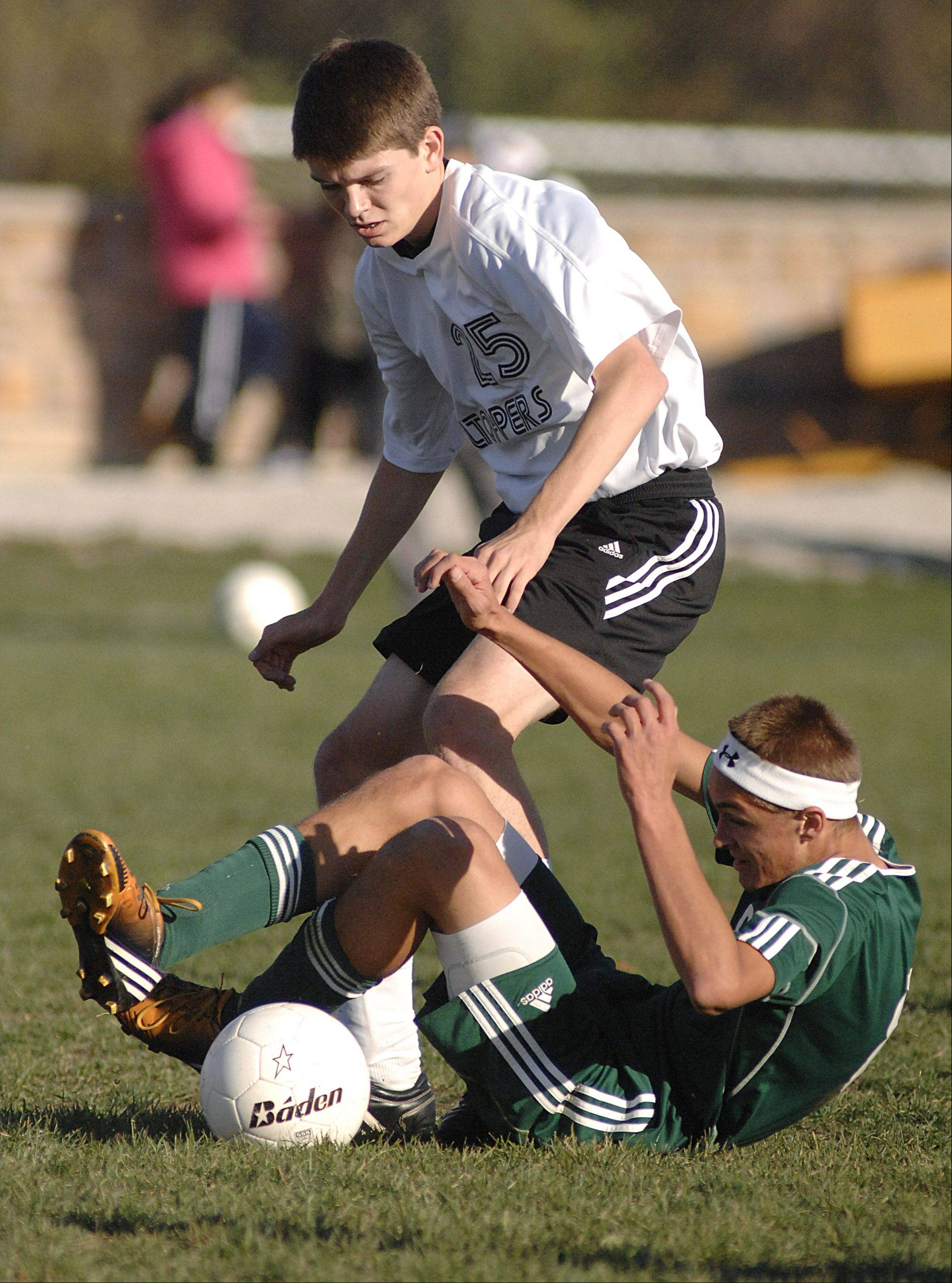 St. Edward's Johnny Shepherd tumbles as he and Elgin Academy's Billy Gracik battle for the ball in the first half on Wednesday, October 10.