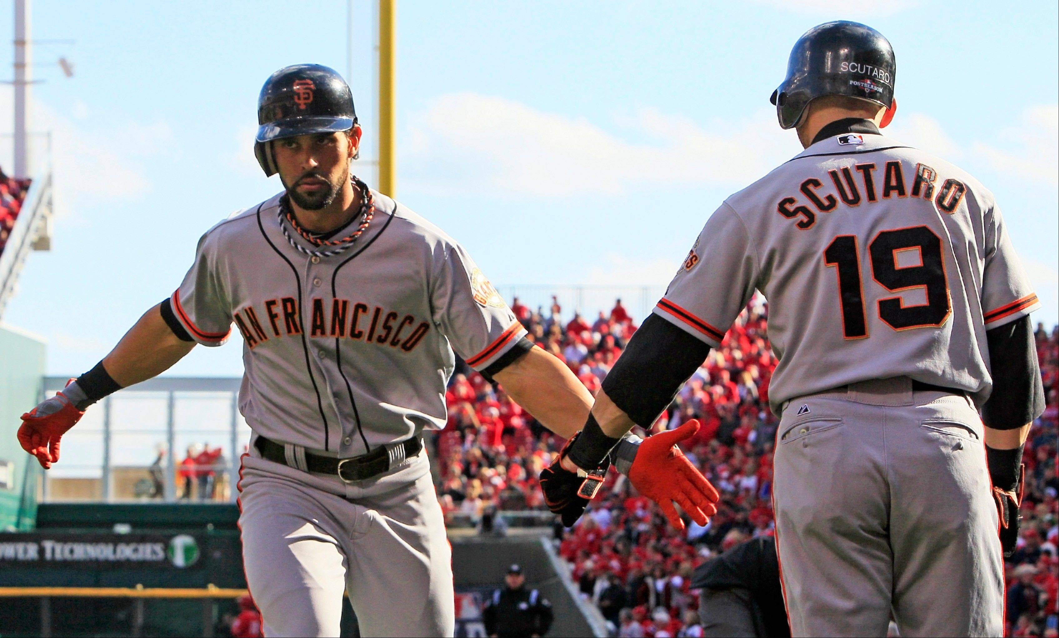 The San Francisco Giants' Angel Pagan is congratulated by Marco Scutaro (19) after Pagan hit a solo home run in the first inning of Game 4 of the National League division baseball series against the Cincinnati Reds on Wednesday in Cincinnati.
