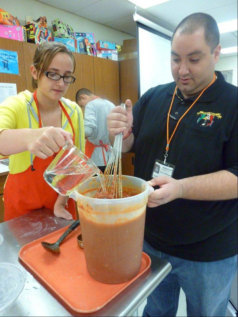 Emily Seidl and Tony DeFilippis of Pizza Bella thin the pizza sauce with a little water.