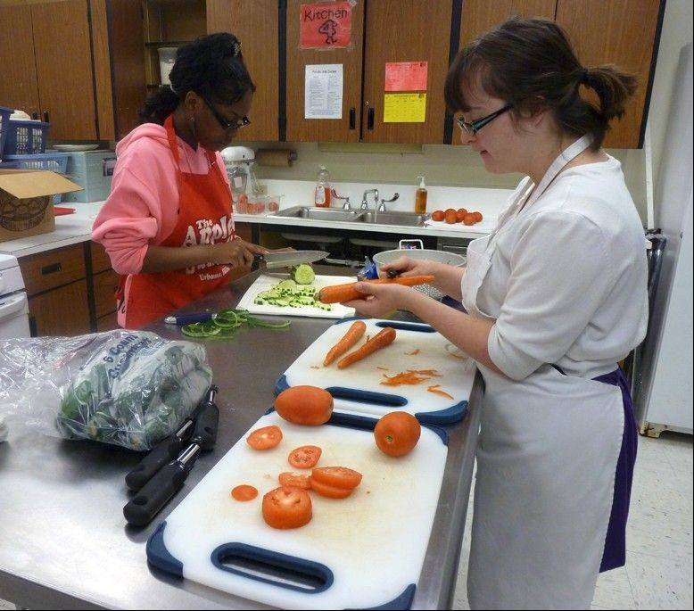Tahkyra Whitaker, left, and Karlee Darow chop vegetables for side salads. Lunches were $6, which included a pizza, salad, dessert and drink.