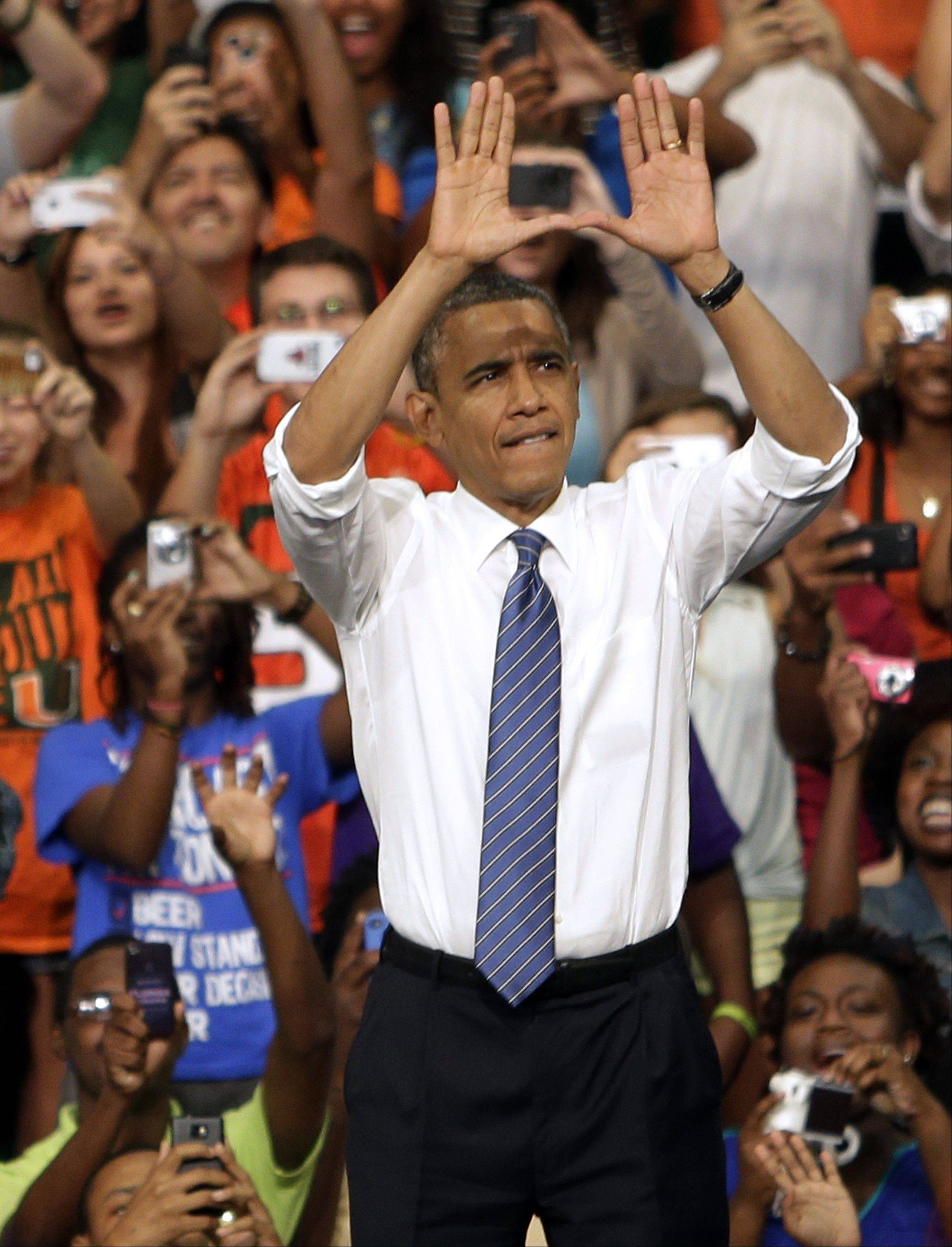 President Barack Obama does the sign of �The U� as he arrives a campaign event at the University of Miami Thursday in Coral Gables, Fla.