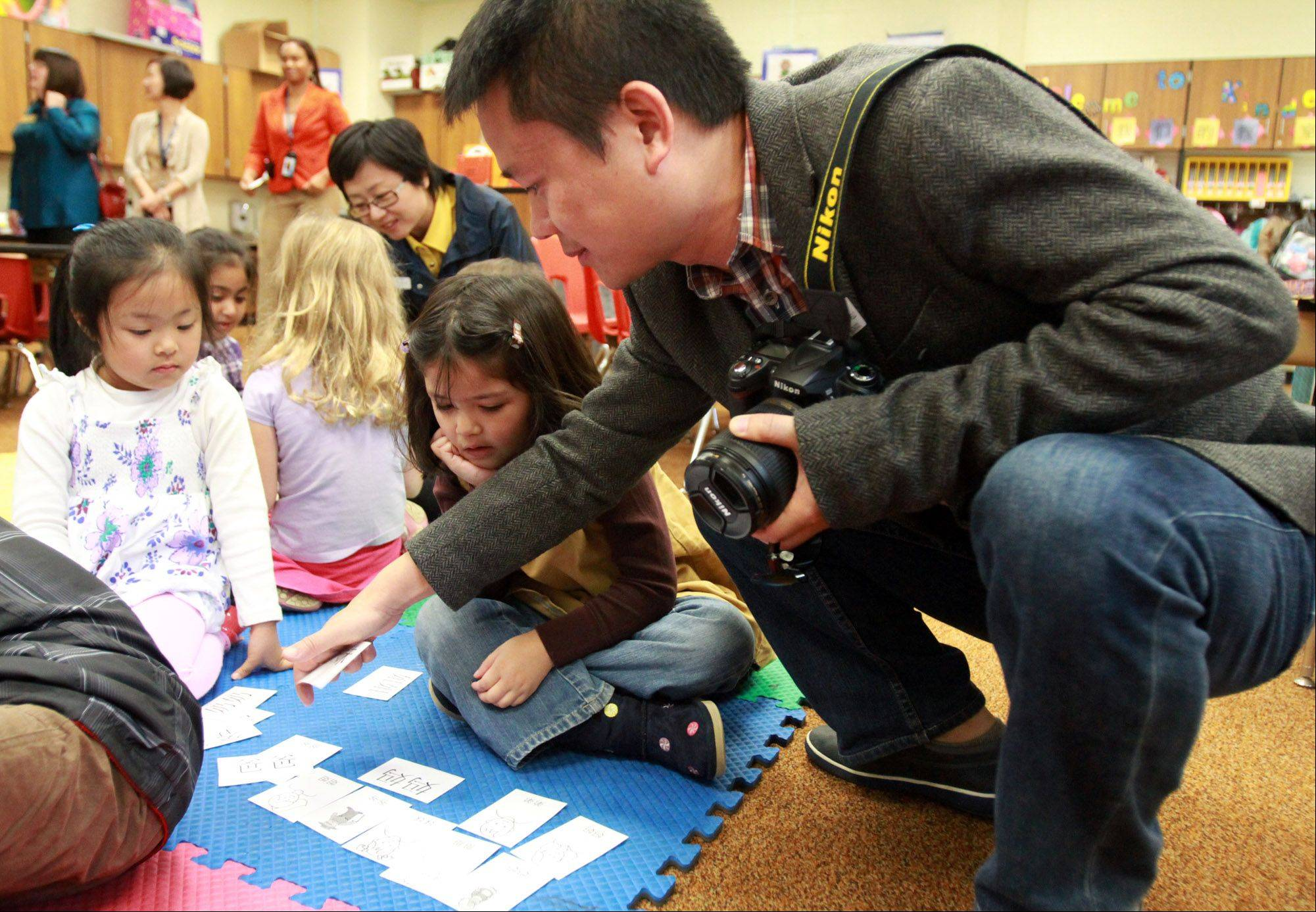 Campanelli Elementary School kindergartners in Angela Kuo�s Chinese immersion class show Chinese language learning cards Thursday to Joe Zhao, deputy division chief with the Bureau of Science and Technology of Guangzhou Municipality as he and other government visitors from Guangzhou, China visit the Schaumburg school.