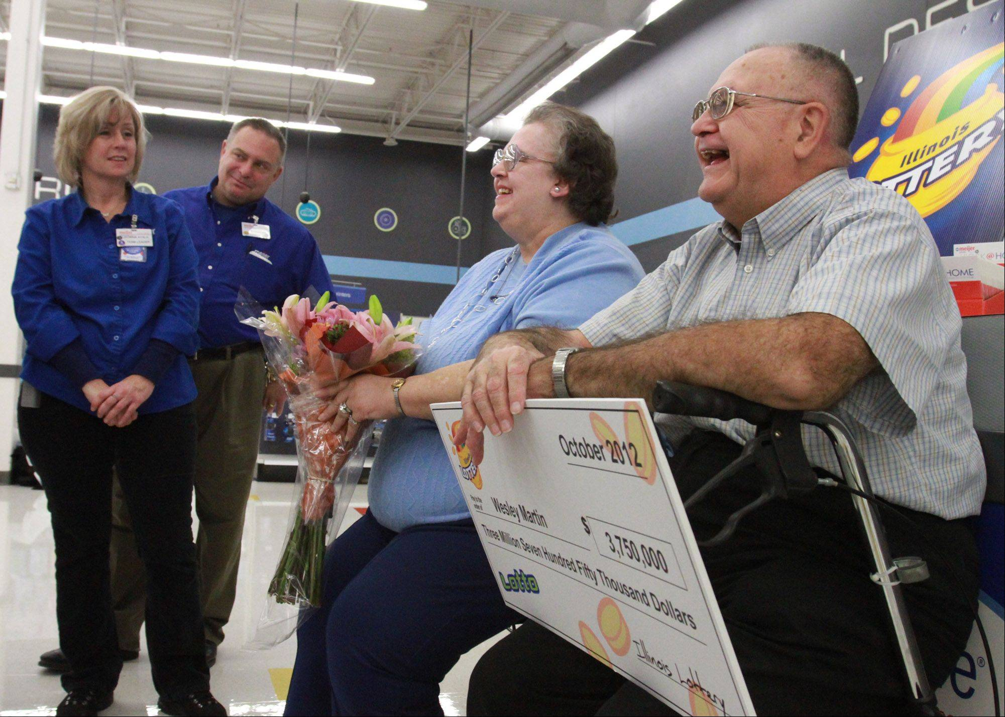 Margaret and Wesley Martin of Palatine celebrate getting their $3.75 million check from the Illinois Lottery on Thursday with employees at Meijer in Rolling Meadows.