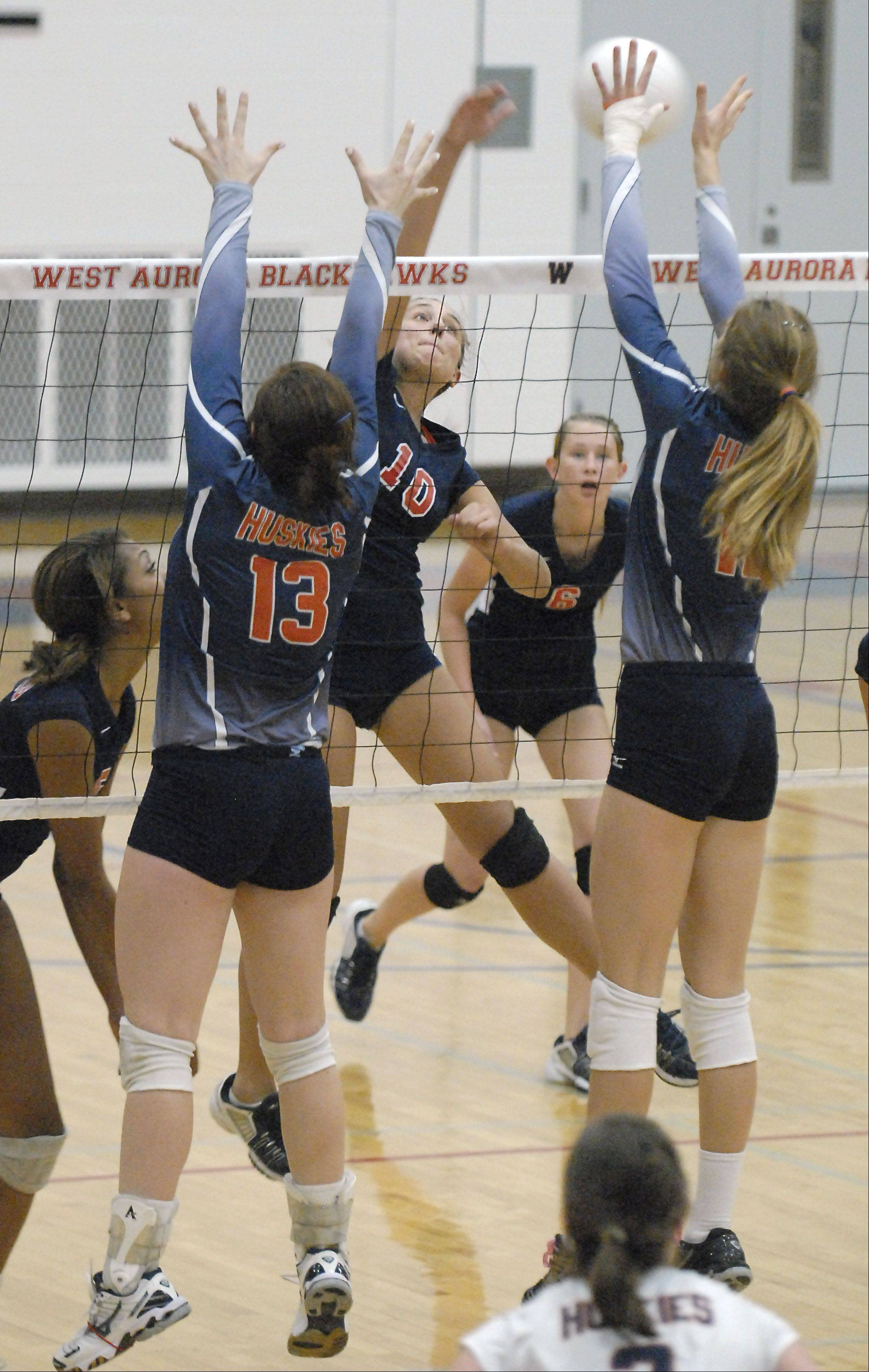 West Aurora�s Kaitlyn Richter spikes the ball over the net toward Naperville North�s Corinne Gajcak, left and Becky Welch, right, in the second game on Thursday, October 11.