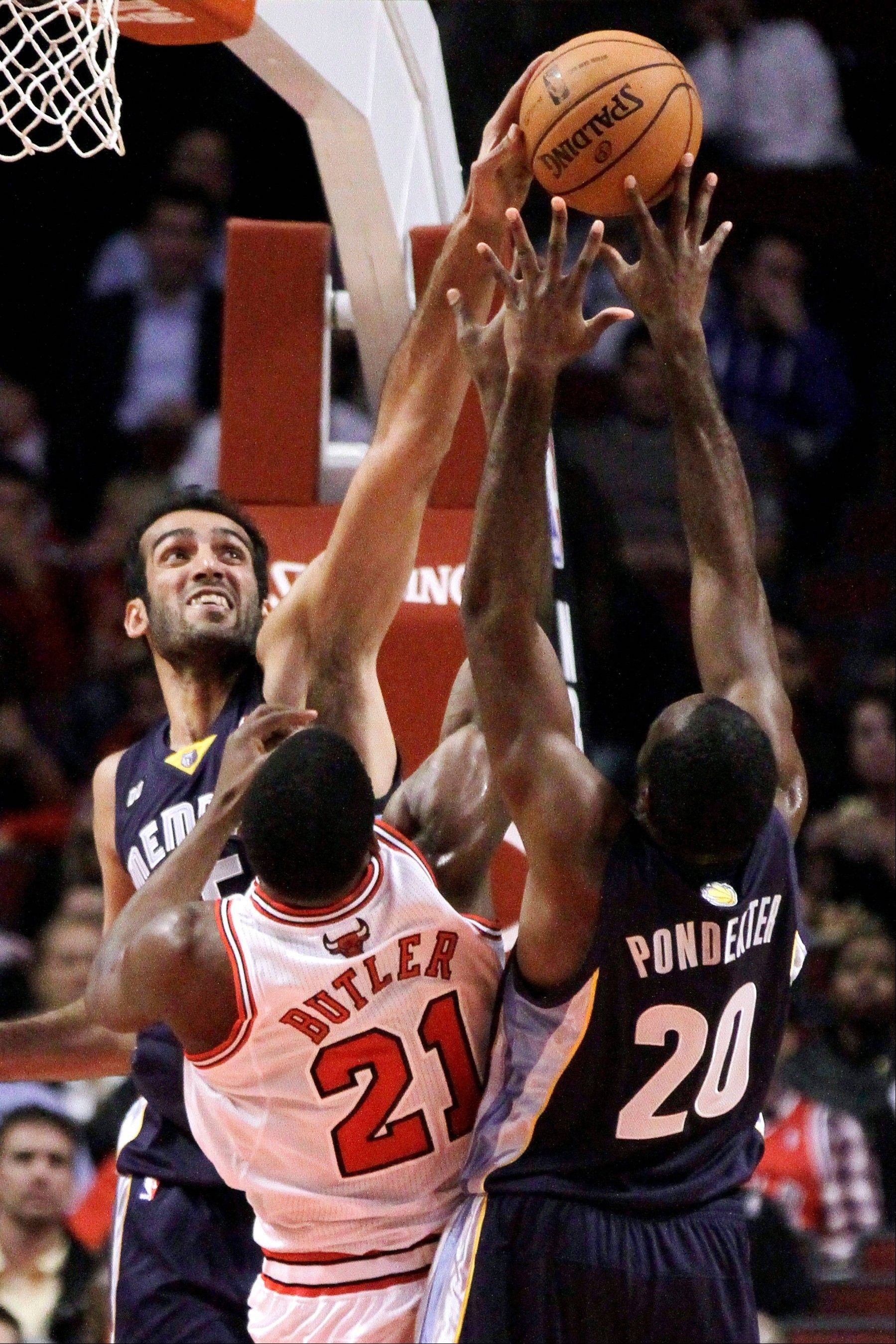 Memphis Grizzlies center Hamed Haddadi, left, blocks the shot of Chicago Bulls guard Jimmy Butler (21) as Grizzlies� Quincy Pondexter (20) defends during the first half of a preseason NBA basketball game, Tuesday, Oct. 9, 2012, in Chicago. (AP Photo/Charles Rex Arbogast)
