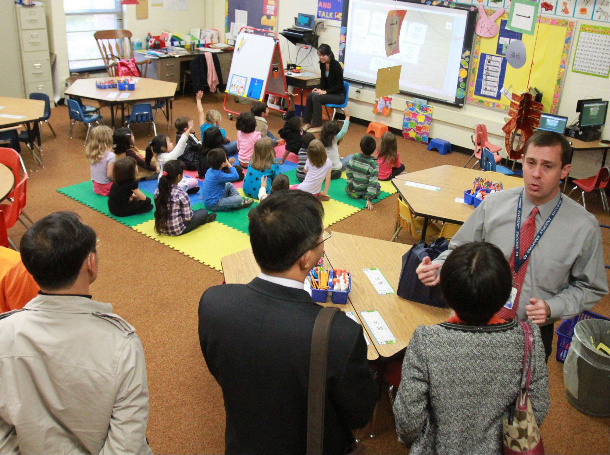 Campanelli Elementary School Principal Stephen Kern, right, shows government visitors from Guangzhou, China Angela Kuo's Chinese immersion class at the Schaumburg school on Thursday.