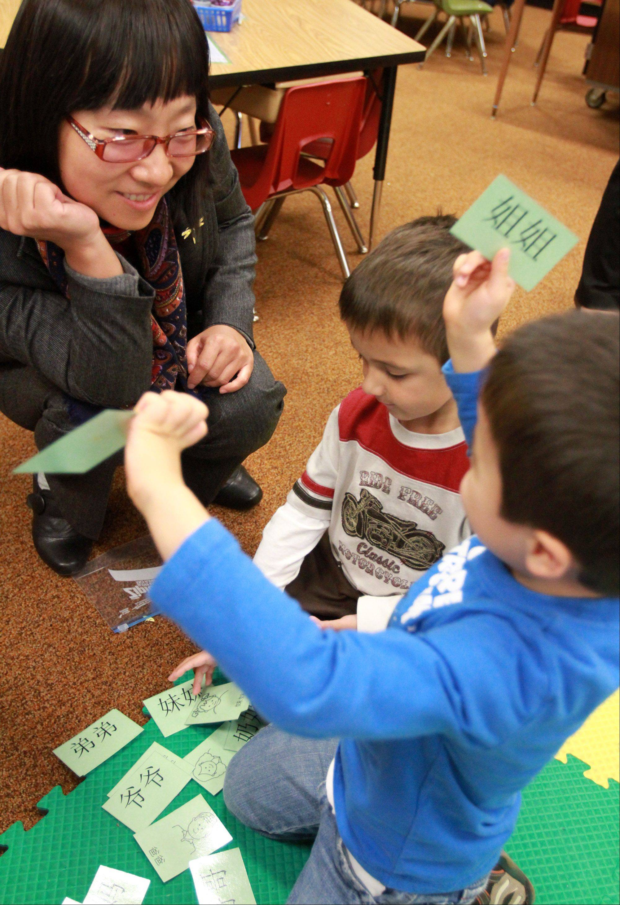 Campanelli Elementary School kindergartners Scott Gilbert, foreground, and Samuel Salazar show Chinese language learning cards Thursday to Sara Gao, division chief with Population and Family Planning Bureau of Guangzhou Municipality as she and other government visitors from Guangzhou, China visit the Schaumburg school.