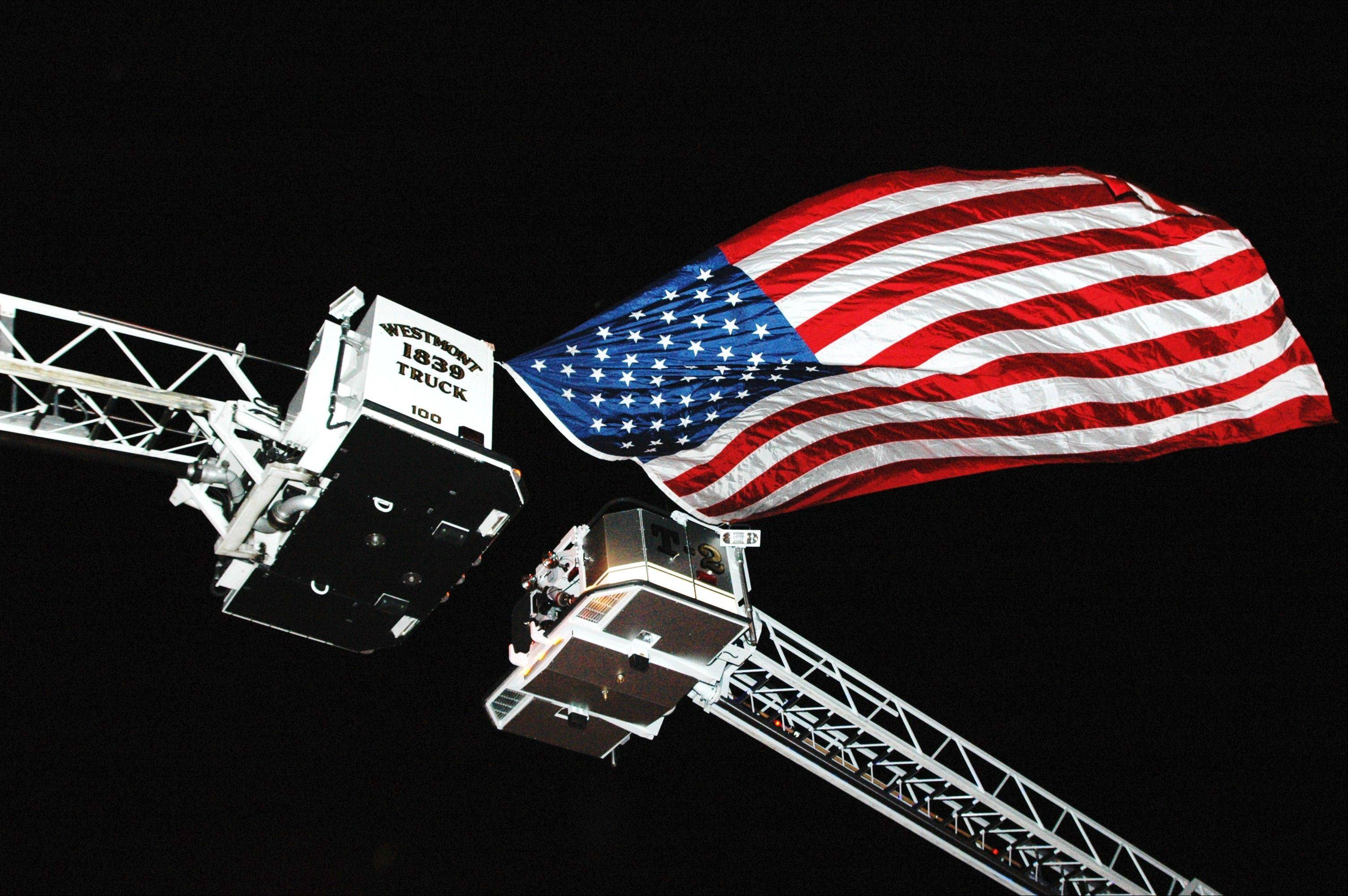 Fire truck ladders are used to hoist an American flag along the route of last year's Silent Parade, honoring fallen firefighters and victims of fire. This year's event includes representatives from 30 departments and begins at 7 p.m. Friday, running along Maple Avenue from Hinsdale to Lisle.