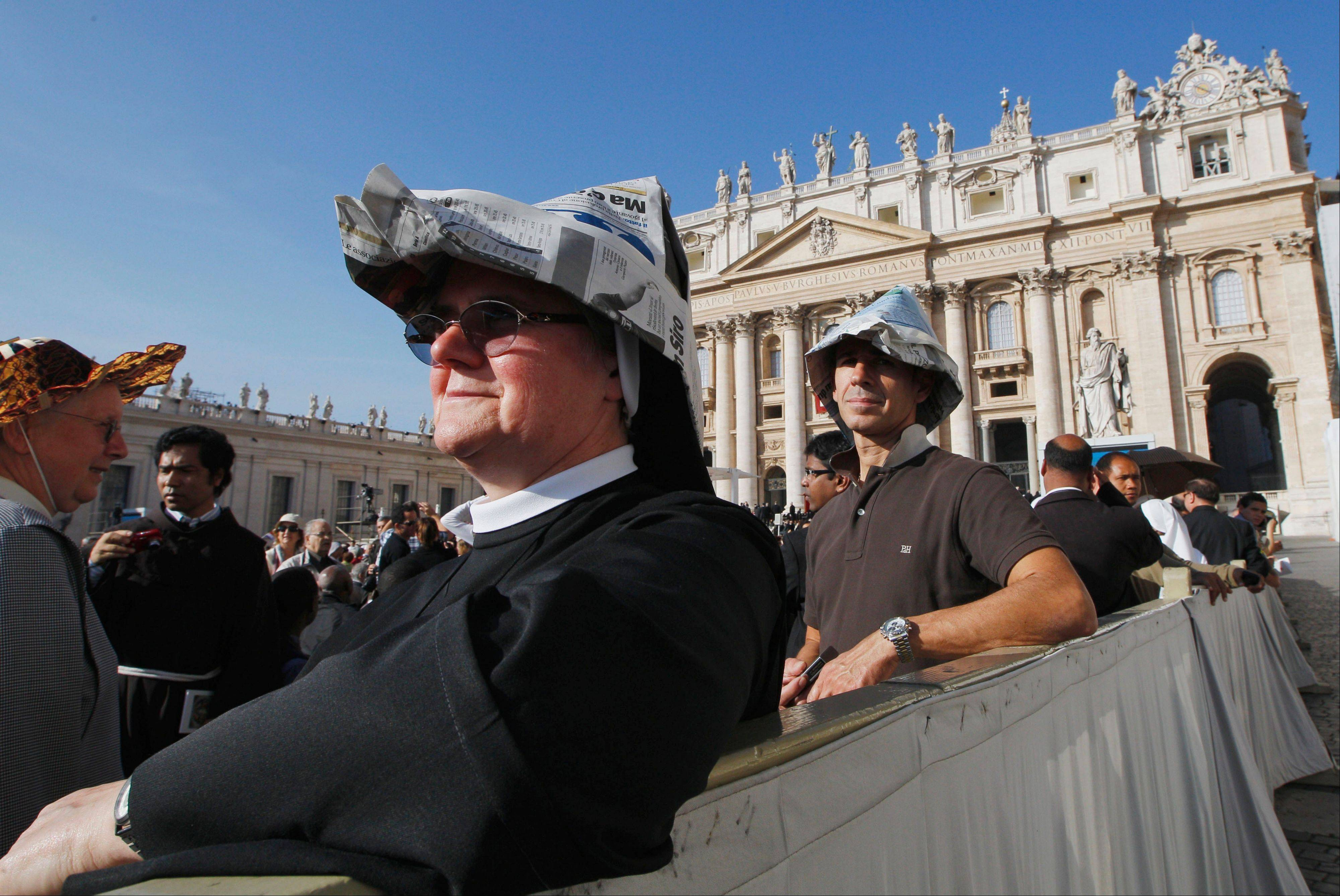 A nun wears a hat made with newspaper pages as she waits for Pope Benedict XVI to celebrate a mass marking the 50th anniversary of the Second Vatican Council, in St. Peter's Square at the Vatican.