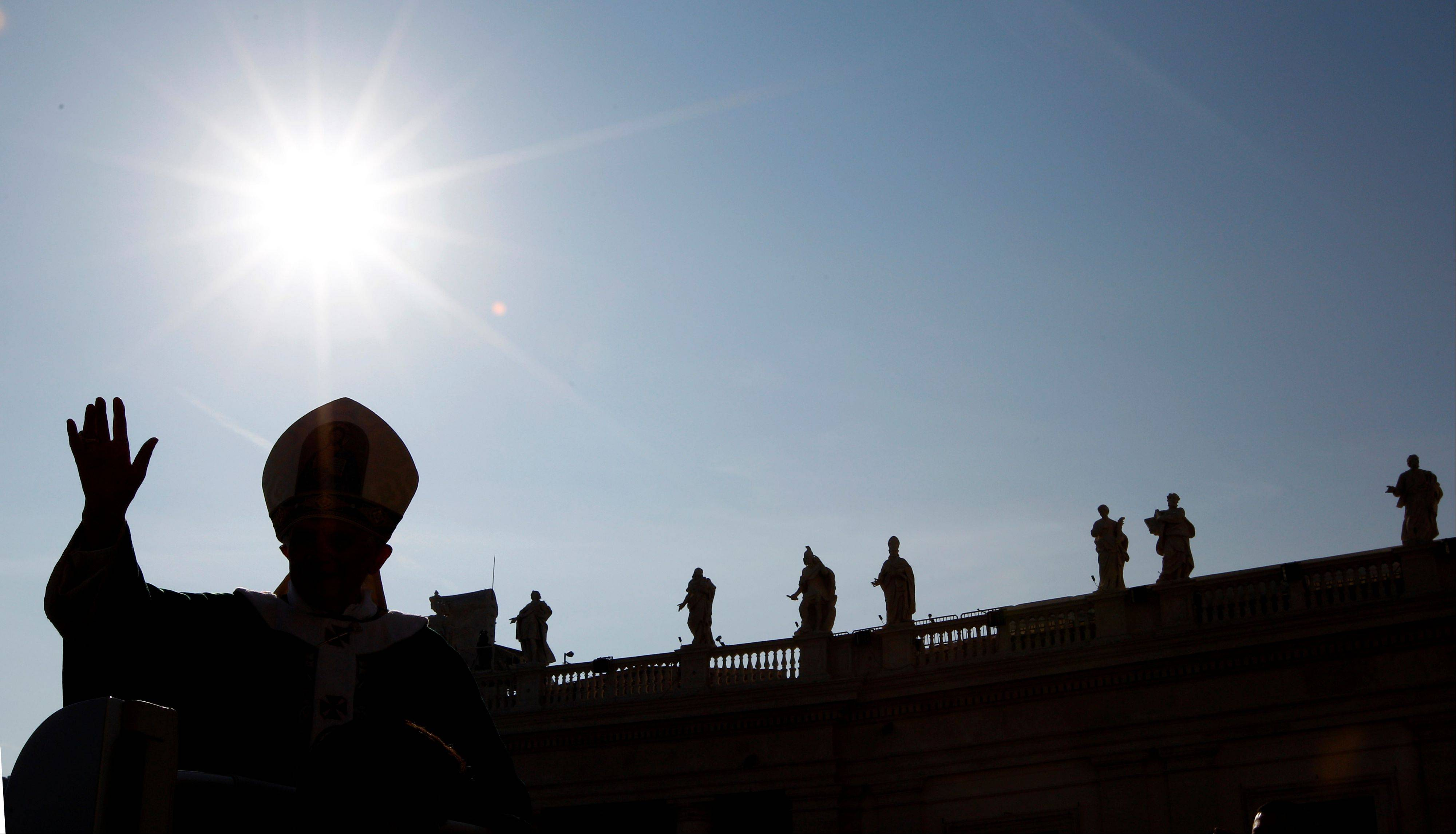 Pope Benedict XVI is silhouetted as he arrives to celebrate a mass marking the 50th anniversary of the Second Vatican Council, in St. Peter's square at the Vatican, Thursday, Oct. 11, 2012.