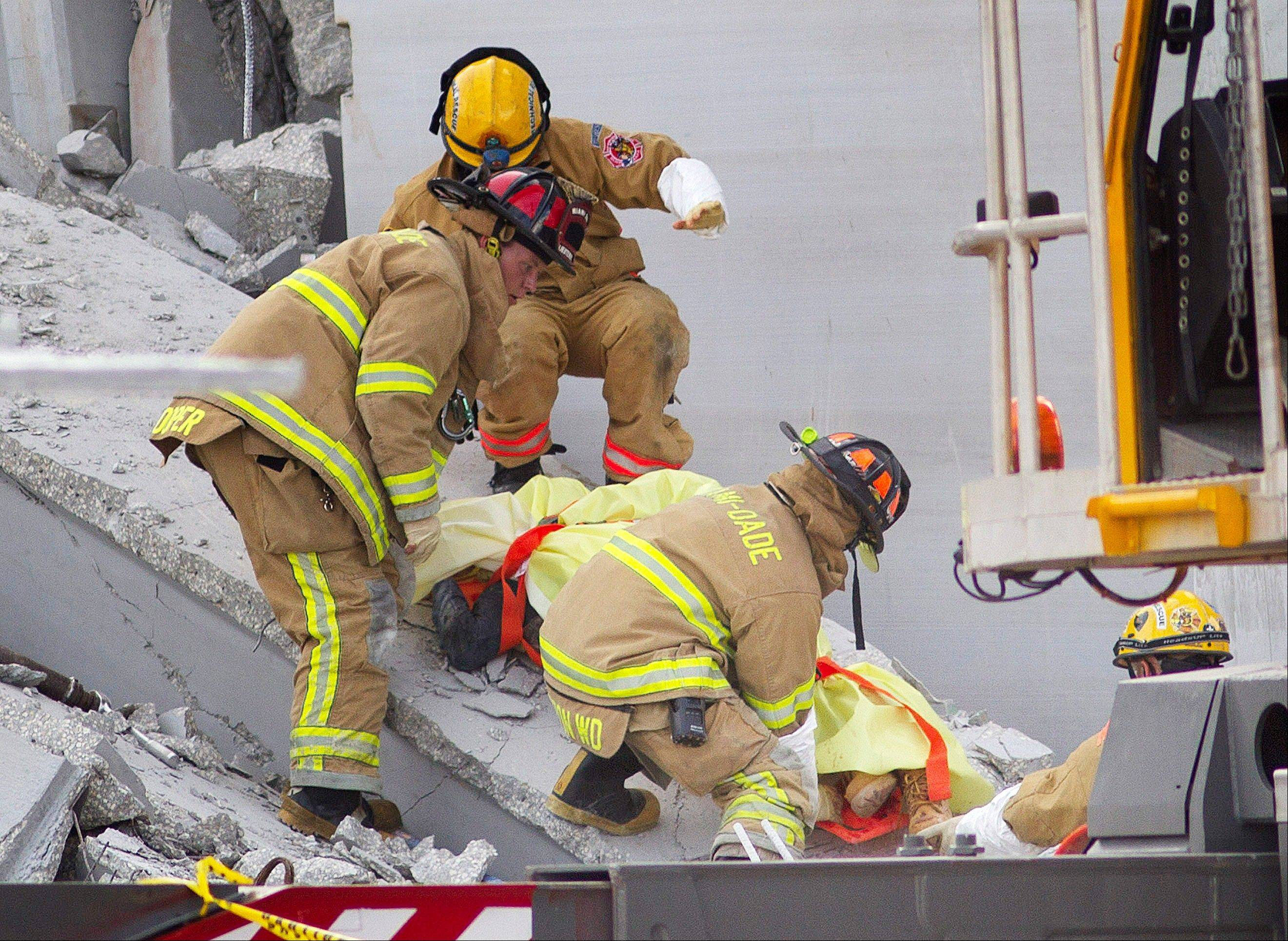 Fire Rescue officials work to remove a victim from the collapsed parking garage at the Miami Dade College West campus in Doral, Fla. Tuesday, Oct. 10, 2012. A section of a parking garage under construction at a community college collapsed killing three people.