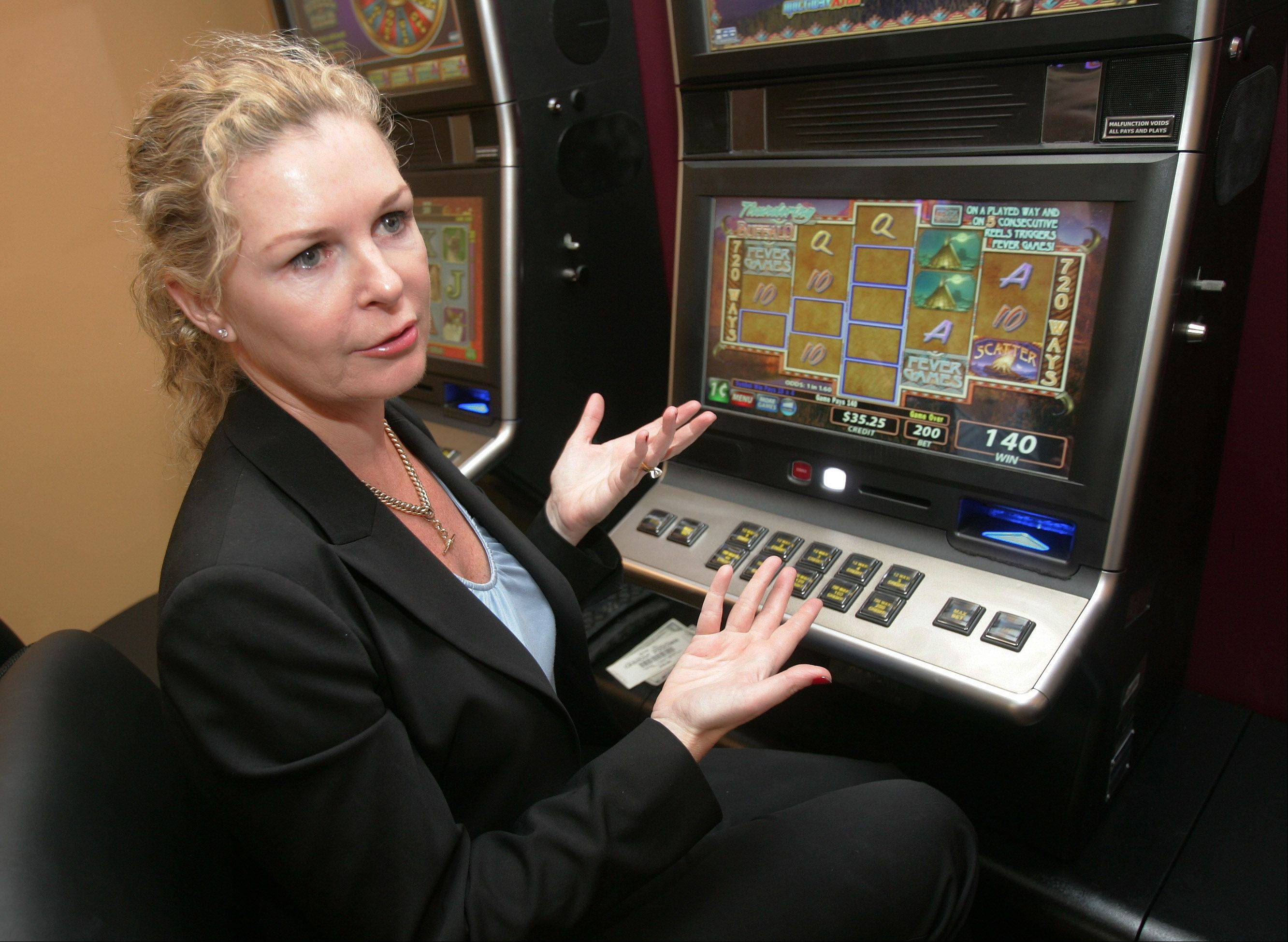 Illinois will keep 30 percent of the net income from the state's new video gambling terminals in restaurants and bars, with the gaming companies and the location owners splitting about 70 percent. Lynne Morris, CEO of Morris Gaming in Skokie, demonstrates the new machines Wednesday at Rosati's of Lakemoor, which is owned in part by Anthony Patti, one of the first business owners to be licensed by the Illinois Gaming Board.