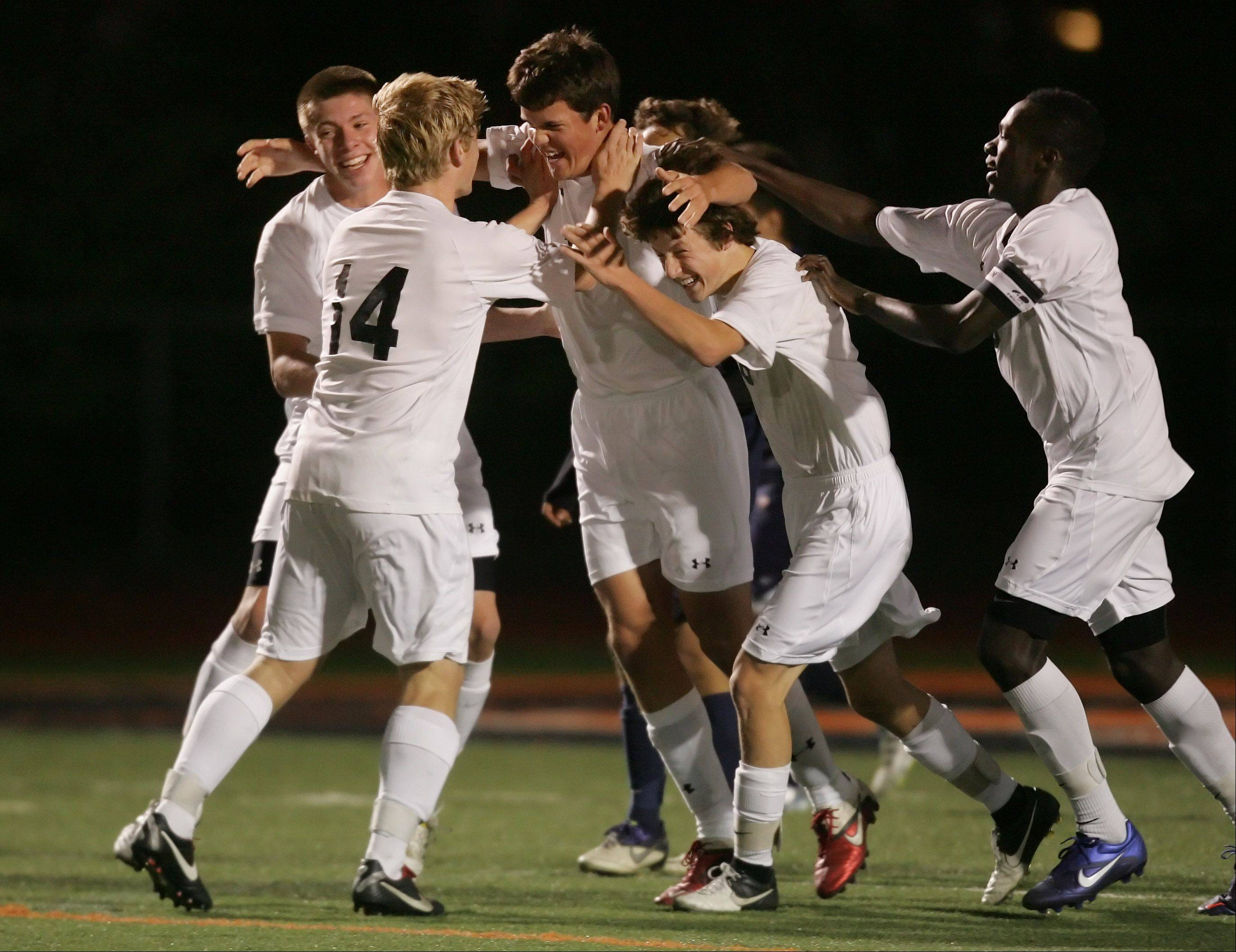 Libertyville players surround Ryan McKenzie, center, after he scored the first goal of Thursday's North Suburban Conference championship game between Round Lake and host Libertyville.