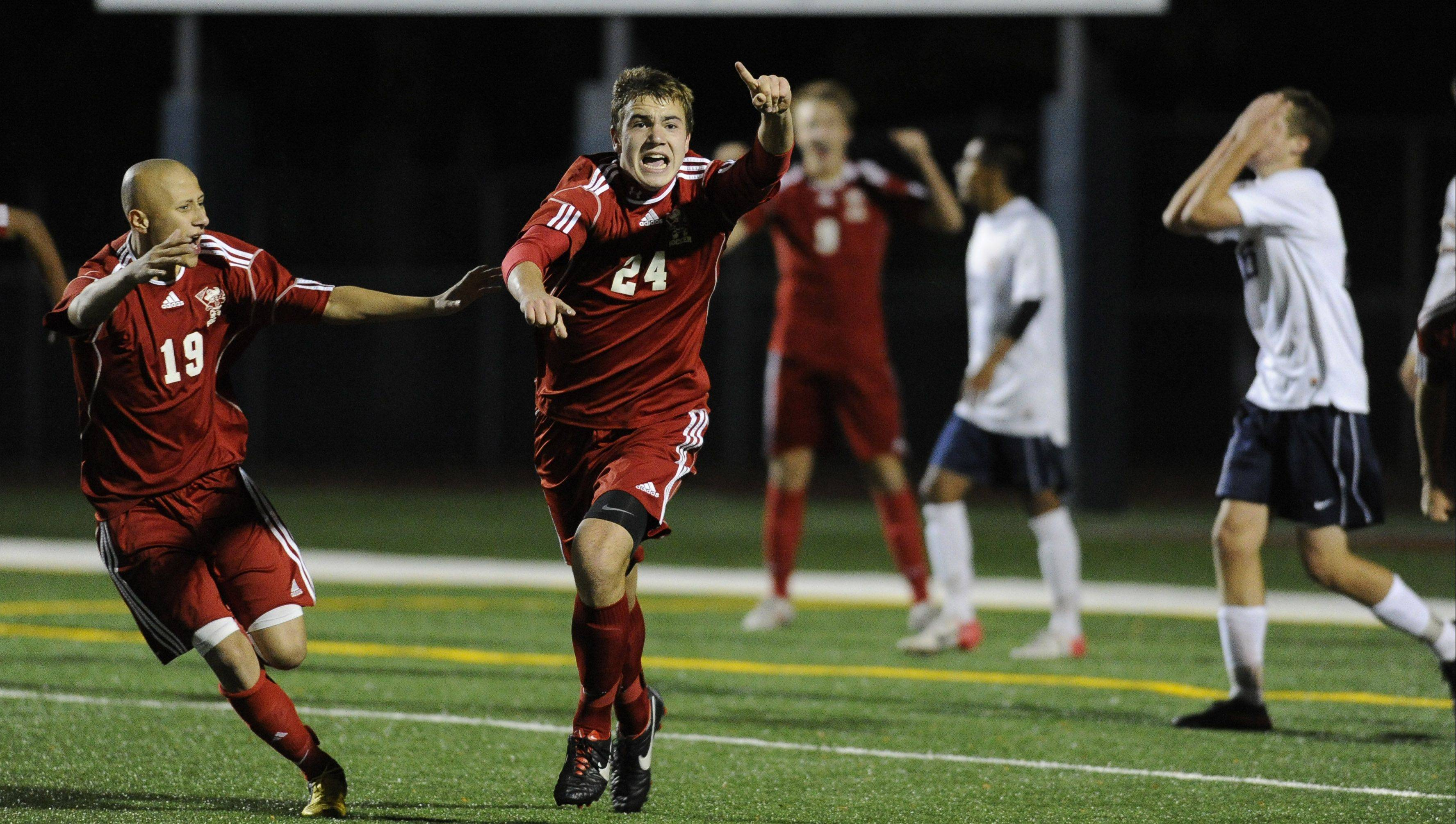Palatine's Jeremy Velinski and his teammates erupt in excitement after evening up the score last in the second period in the Mid-Suburban League championship game at Buffalo Grove High School on Thursday. The Pirates later claimed victory in penalty kicks.