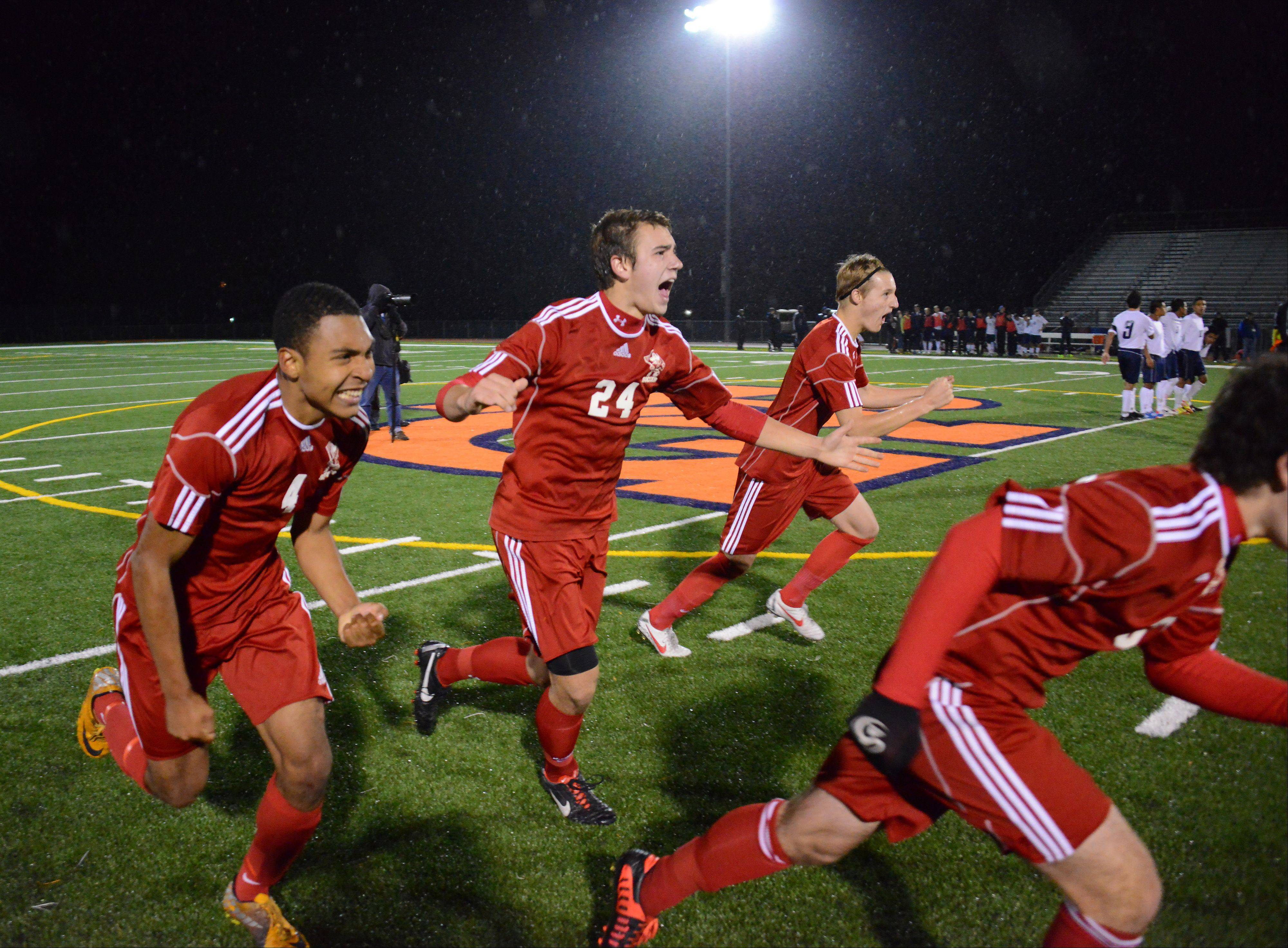 Palatine's Jeremy Velinski and his teammates erupt in excitement after the winning shootout goal in the Mid-Suburban League championship game at Buffalo Grove on Thursday.