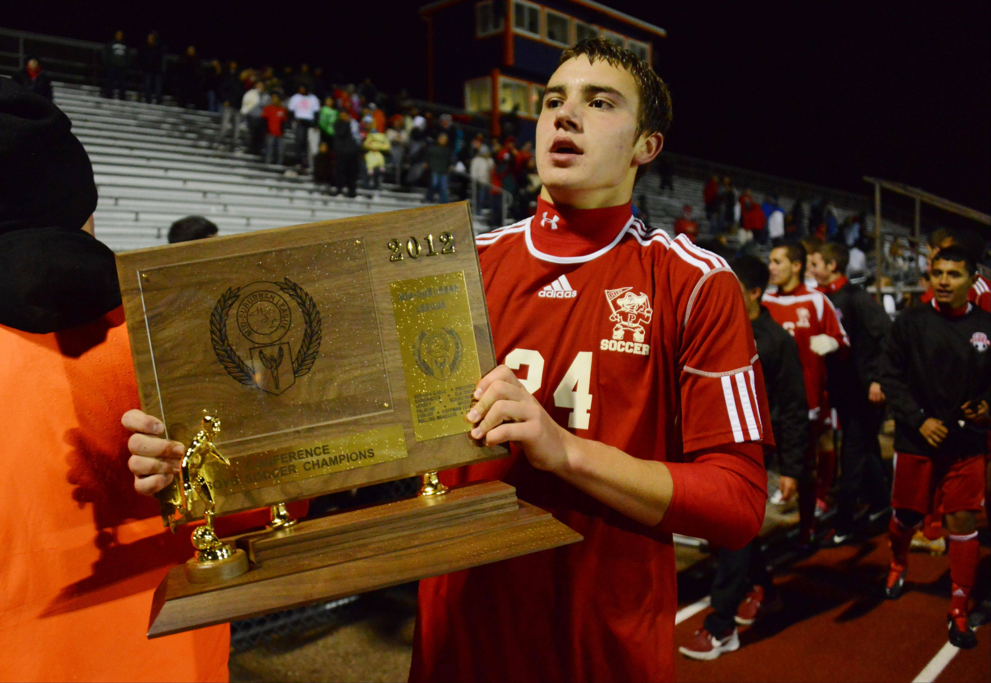 Palatine's Jeremy Velinski holds the league championship trophy after the Pirates edged Buffalo Grove in shootout Thursday at BG.