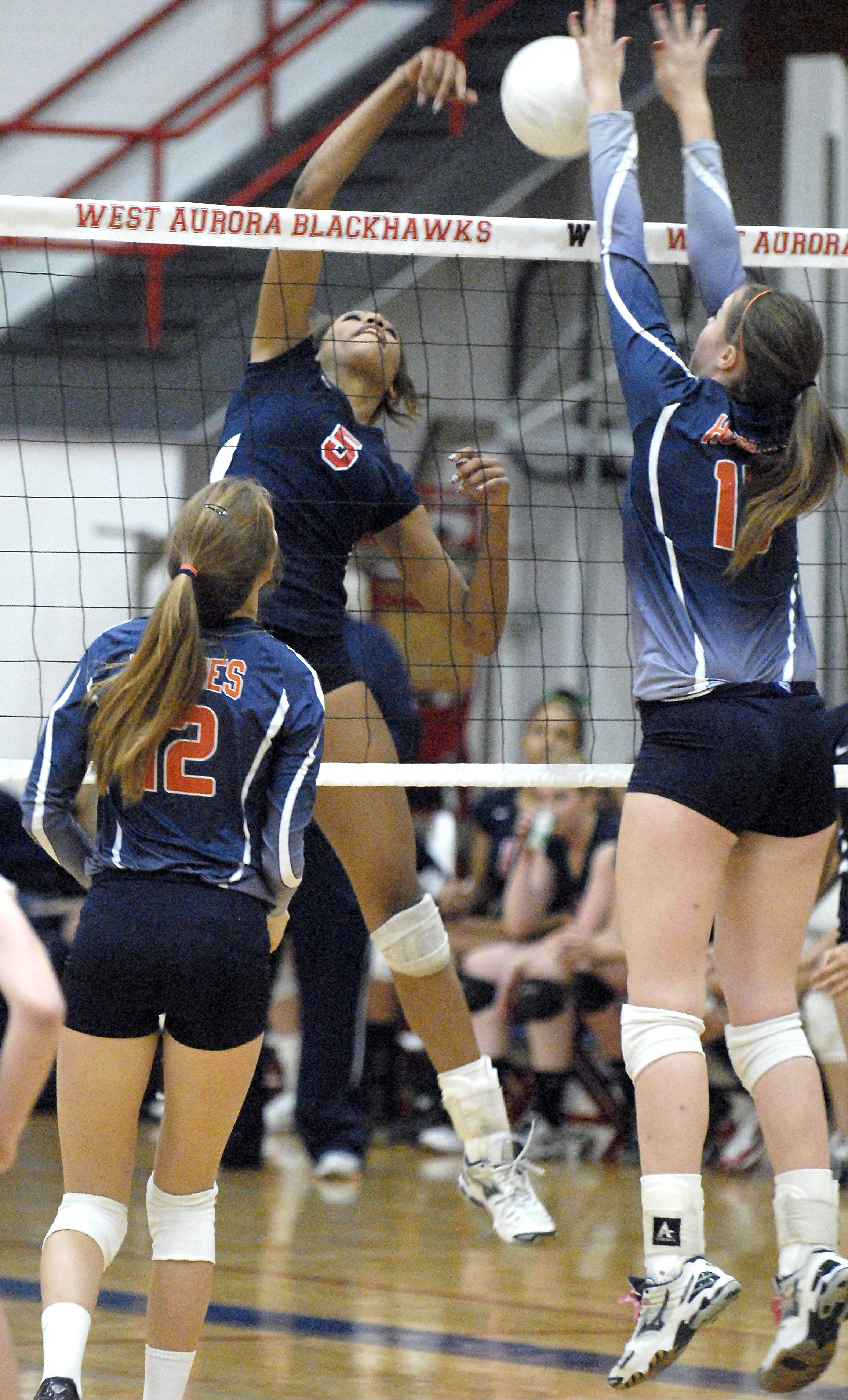 West Aurora's Nerissa Vogy's spike is met by a block by Naperville North's Maddi Henry in the first game on Thursday, October 11.