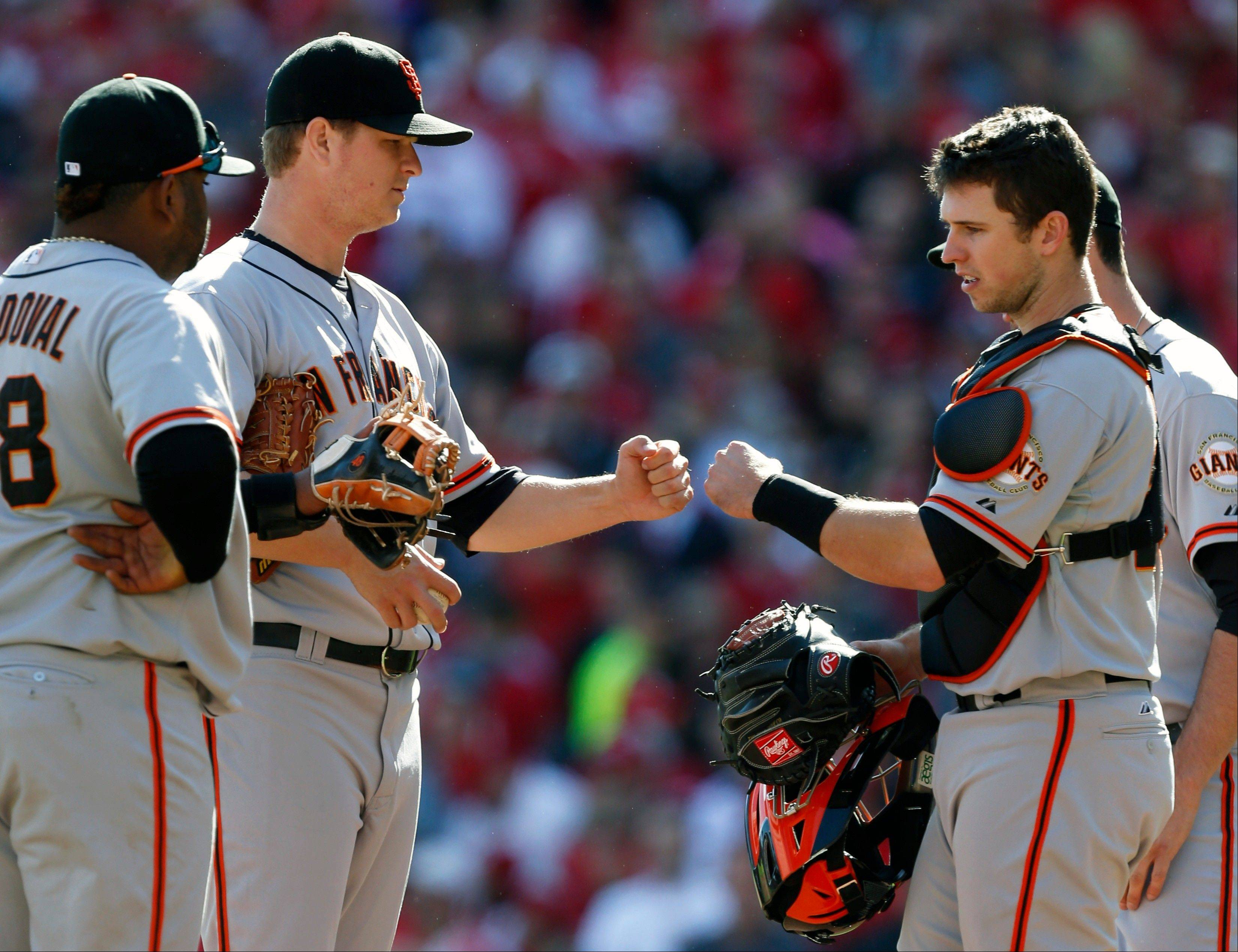 San Francisco Giants starting pitcher Matt Cain, center left, fist bumps catcher Buster Posey, right, as Cain was taken out Thursday during the sixth inning of Game 5 of the National League division baseball series.
