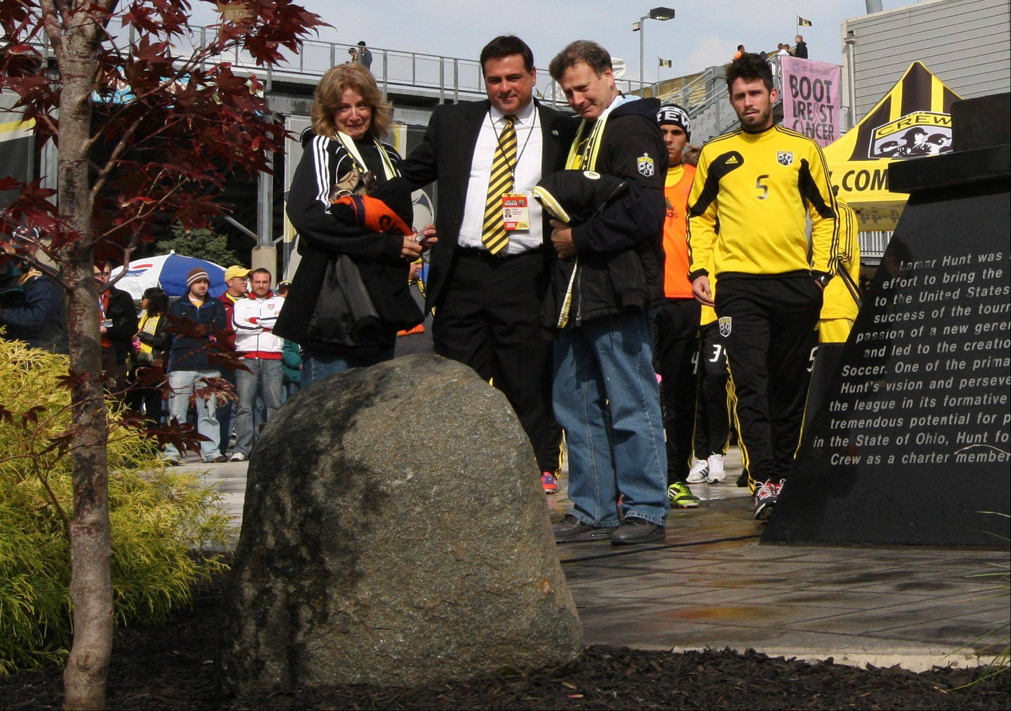 Crew president and general manager Mark McCullers stands between former Columbus Crew player Kirk Urso's parents, Sandy and Mike, after a dedication ceremony Sunday at Founder's Park to honor Kirk, who died at age of 22 of a congenital heart defect. The Crew has established a memorial fund in Urso's honor to support research and programming focused on congenital heart defects and sudden cardiac death in youth.