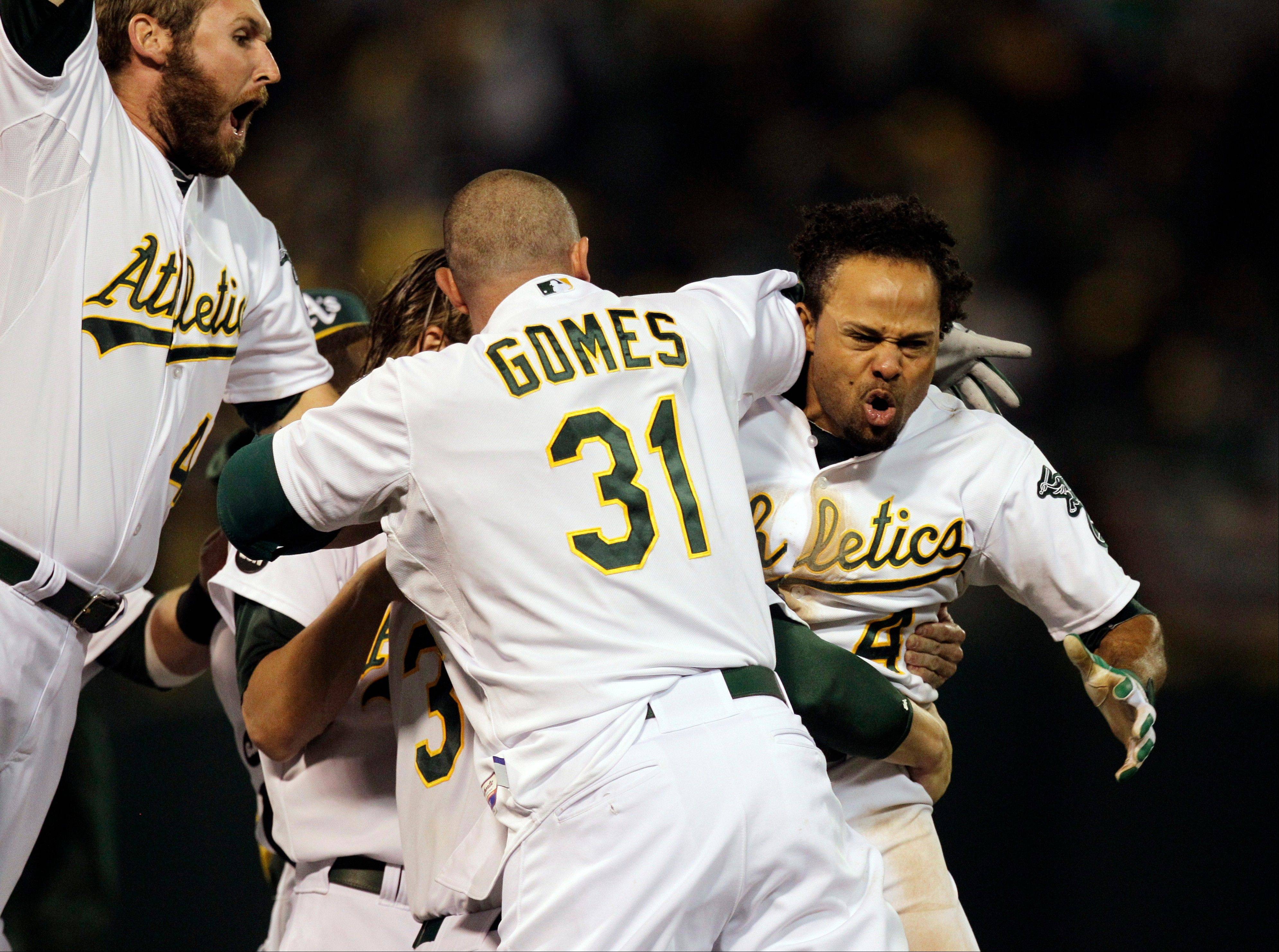 Oakland Athletics left fielder Coco Crisp, right, celebrates Wednesday after hitting a single to score Seth Smith and win the game 4-3 in Game 4 of an American League division baseball series against the Detroit Tigers in Oakland, Calif.