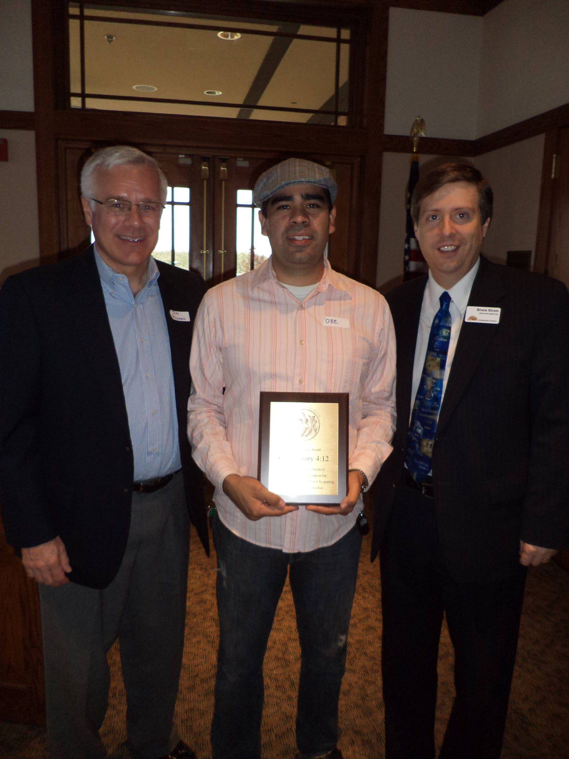 On Oct. 3, Campus Pastor Obe Arellano from Community Christian Church (center) accepts the Administer Justice Annual Barnabas Award from Board Chair Jim Pluymert, left, along with Executive Director Bruce Strom.