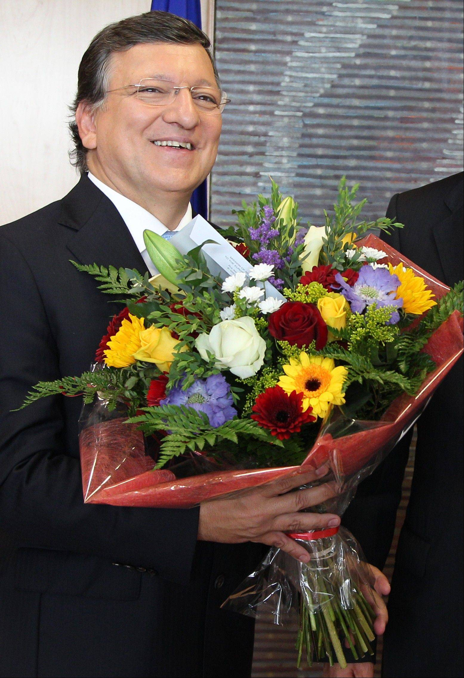 European Commission President Jose Manuel Barroso reacts, as he received flowers by Norway�s ambassador to the EU Atle Leikvoll, after the 2012 Nobel Peace Prize was given to the EU, at the European Commission headquarters in Brussels, Friday.