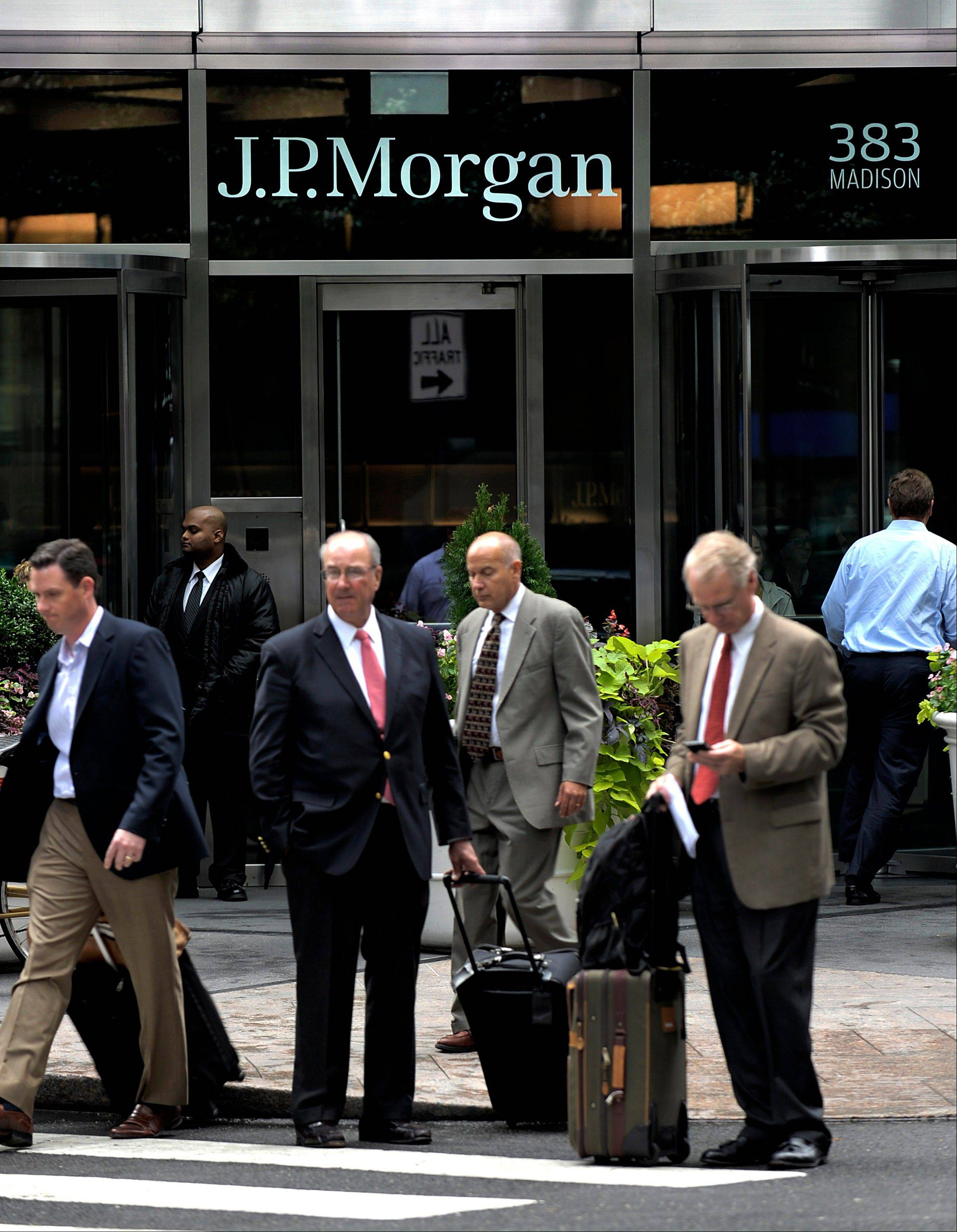 Pedestrians stand in front of a JPMorgan & Chase Co. office in New York, U.S.