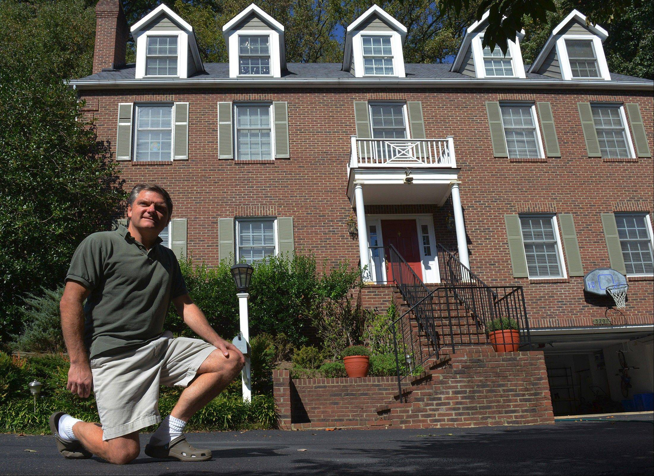 John Bristol outside his Maryland house, where using clear plastic sheeting on his single-pane windows also helped winterize his home.