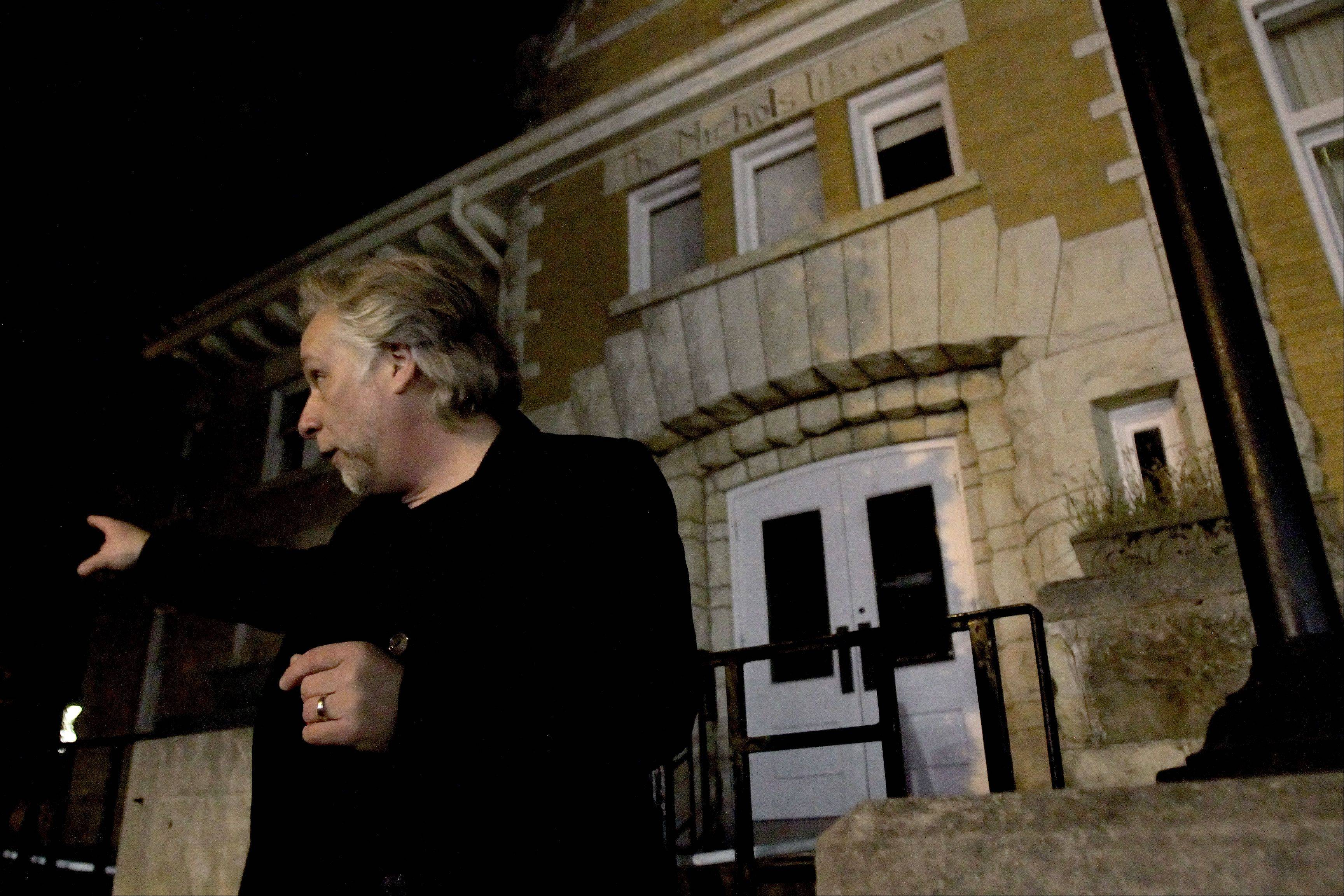 Kevin Frantz tells a ghost story outside the old Nichols Library as leads Naperville's Official Ghost Tour.