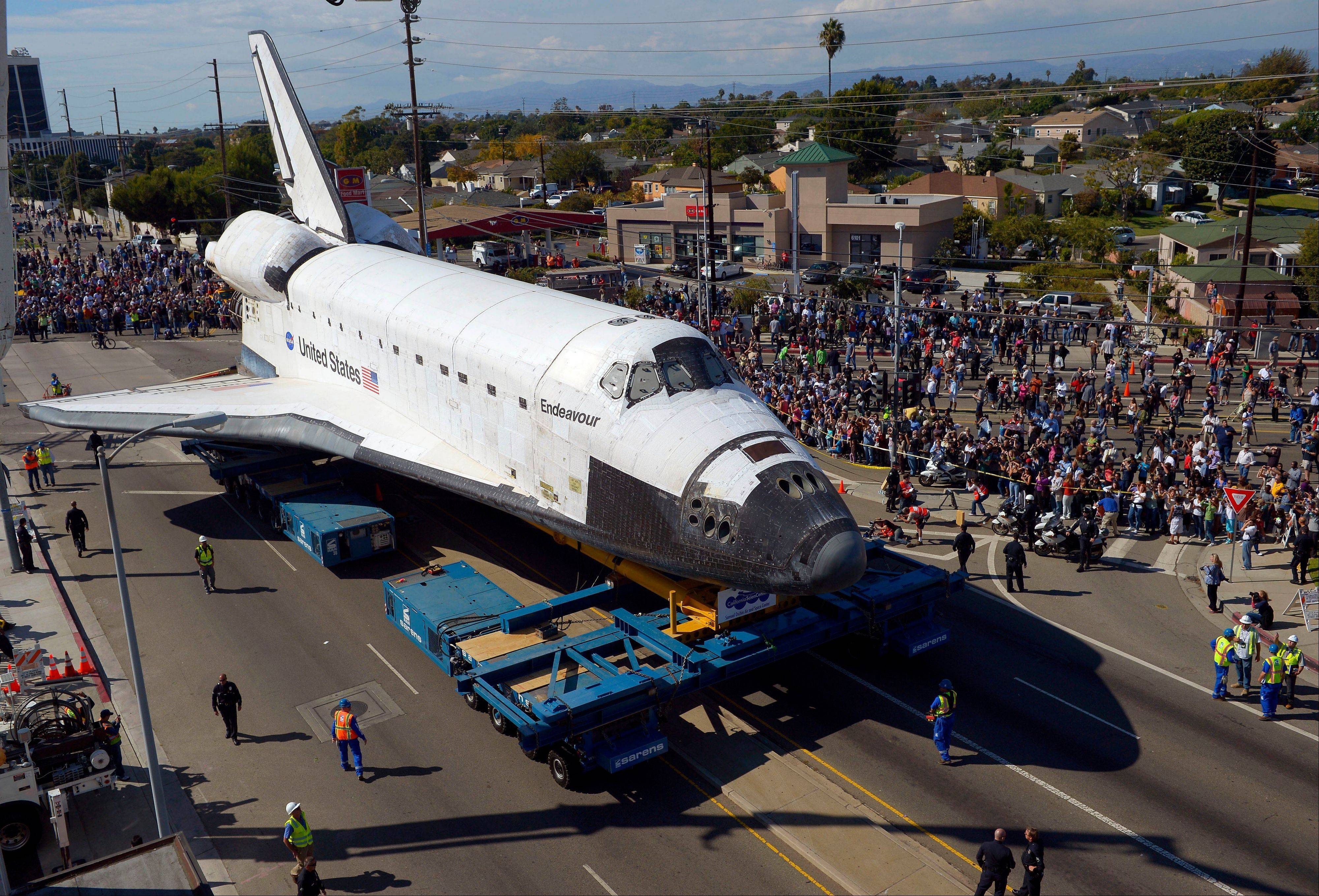The Space Shuttle Endeavour slowly moves along city streets on a 160-wheeled carrier, Friday, Oct. 12, 2012, in Los Angeles.