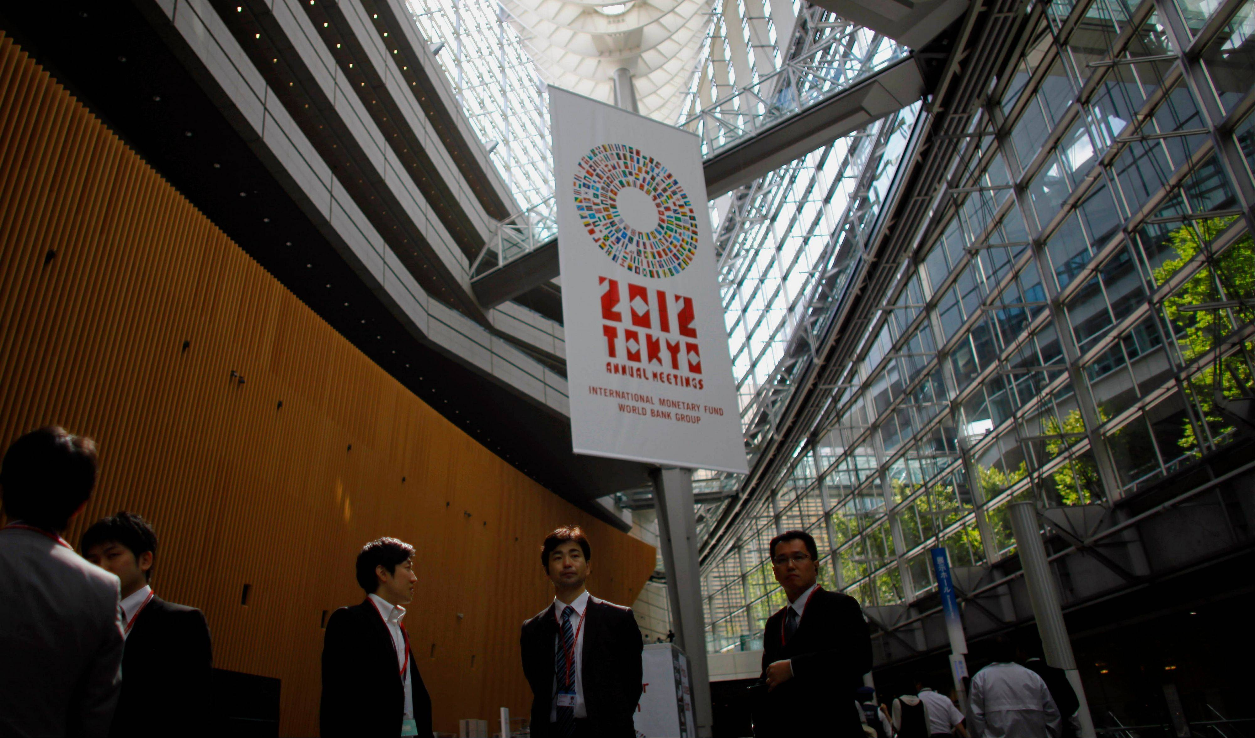 People hang out at the venue of the IMF meeting in Tokyo. When global finance ministers meet this week in Tokyo, they'll confront a triple challenge: Economic troubles in three major regions are threatening the world's economy.