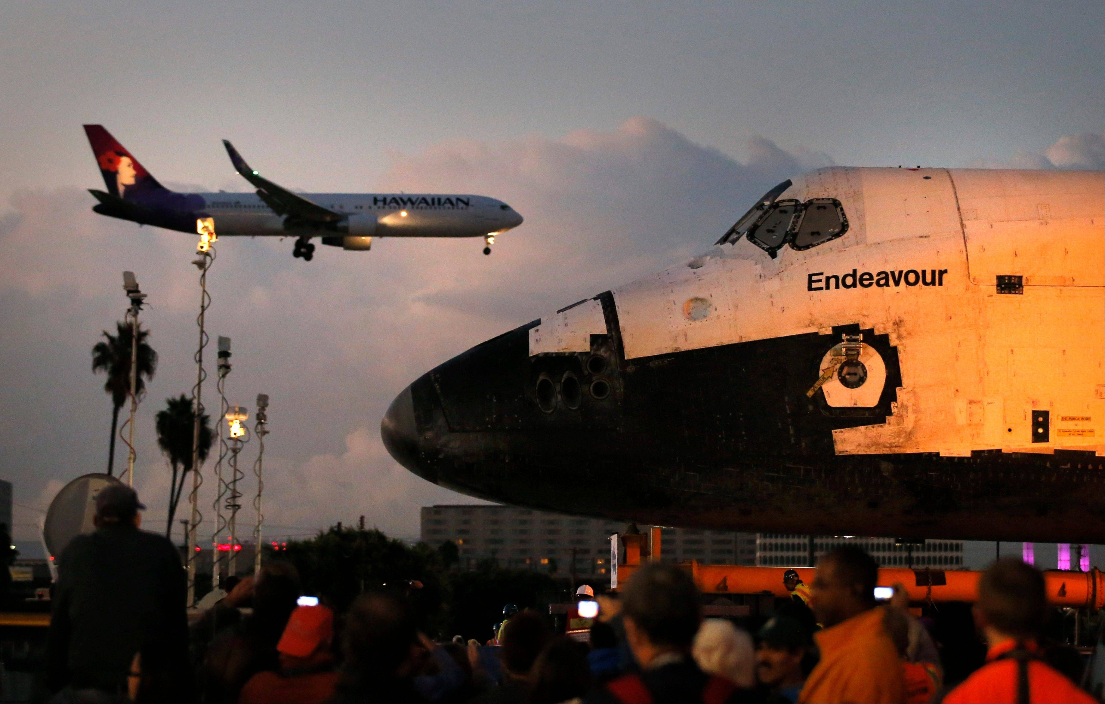 The space shuttle Endeavour sits in a strip mall as a Hawaiian Airlines jet approaches a runway at Los Angeles International Airport in Los Angeles, Friday, Oct. 12, 2012. Endeavour's 12-mile road trip kicked off shortly before midnight Thursday as it moved from its hangar at the airport en route to the California Science Center, its ultimate destination.