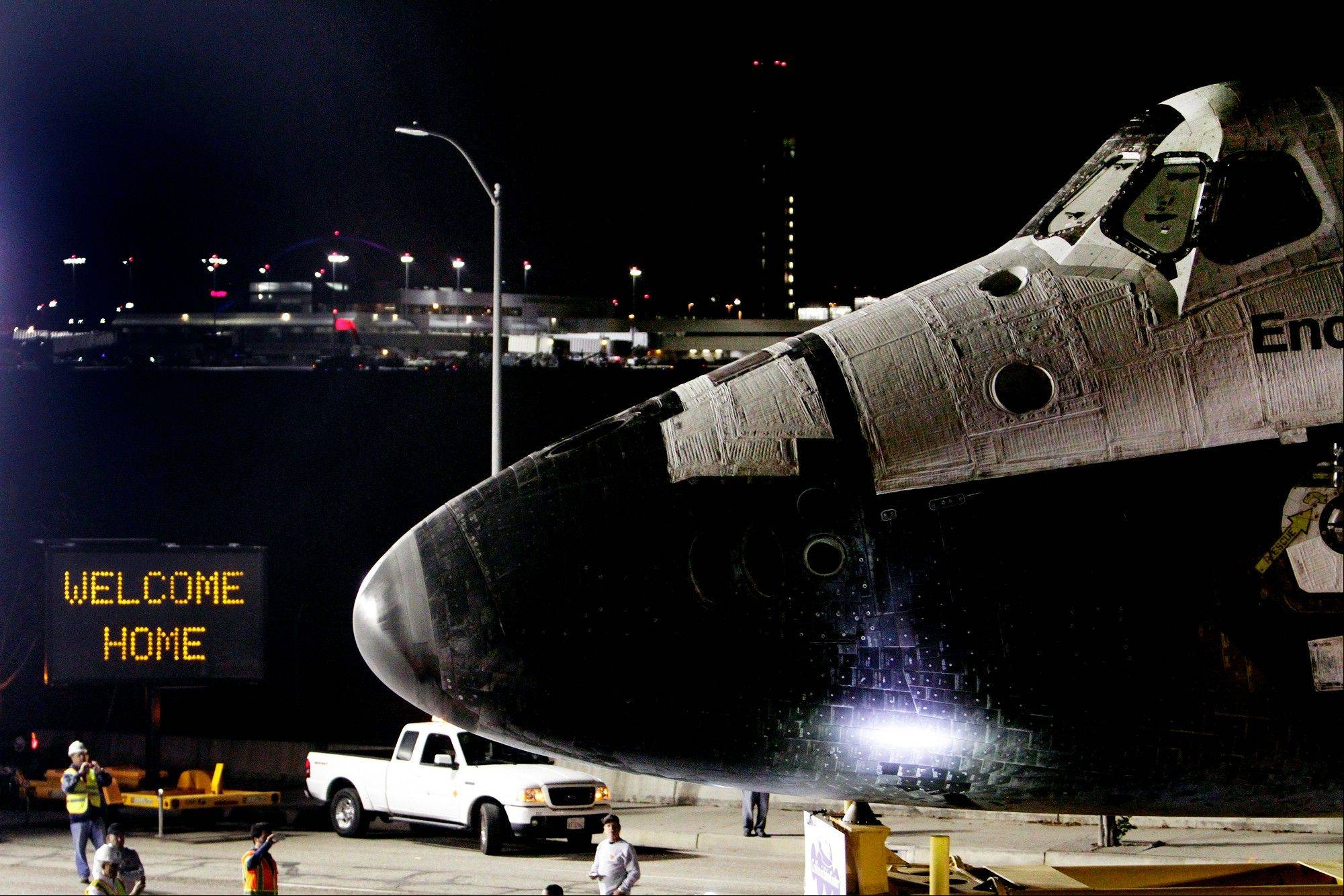 A welcome home sign is displayed on the turn as space shuttle Endeavour leaves a hanger at Los Angeles International Airport en route to the California Science Center in Los Angeles Friday, Oct. 12, 2012. Endeavour's 12-mile road trip to its ultimate destination kicked off shortly before midnight Thursday.