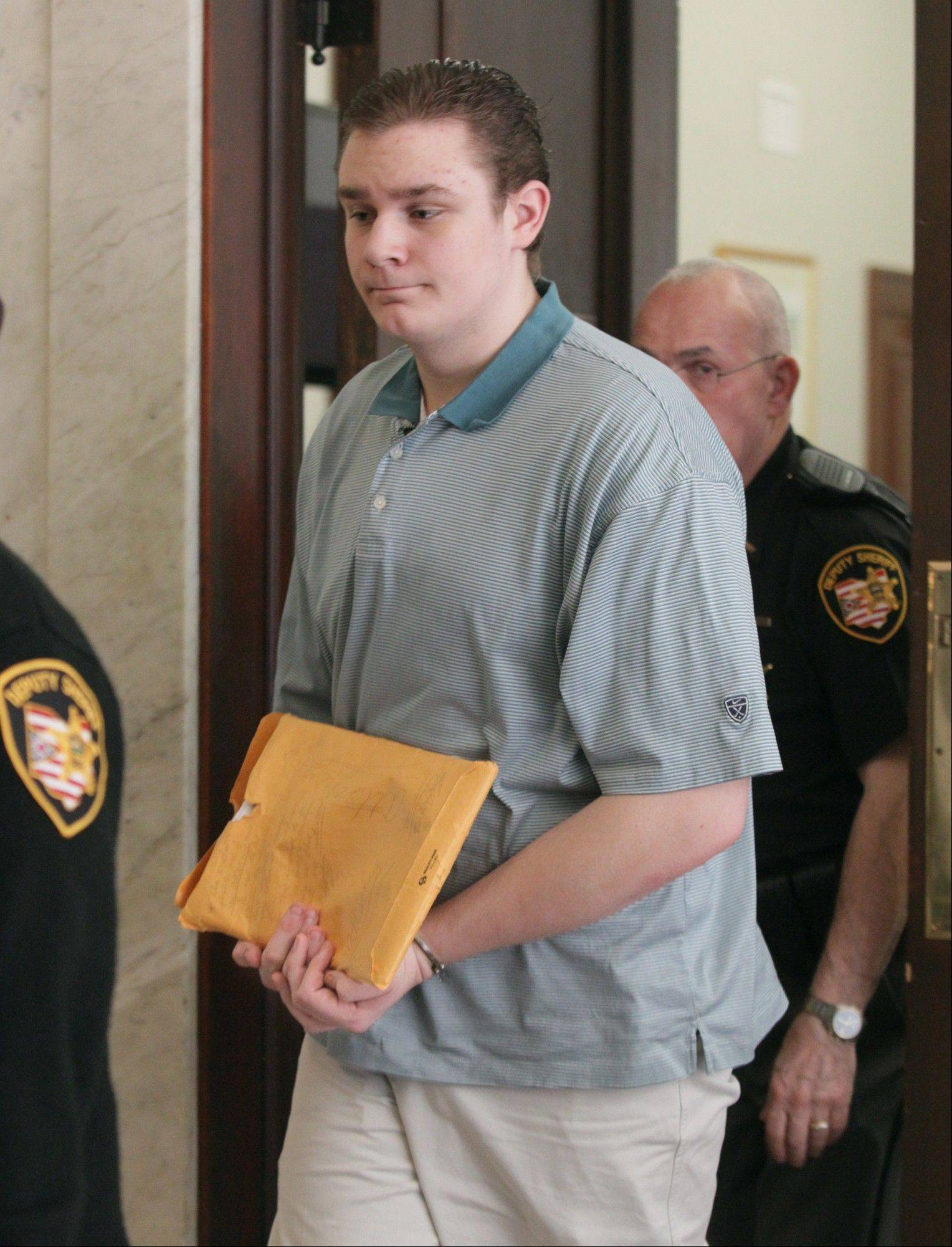 Brogan Rafferty, 17, is escorted by police Friday from the Summit County Common Pleas Courtroom in Akron, Ohio. Rafferty and an adult accomplice are charged with three killings in a plot to lure victims through phony Craigslist job offers.