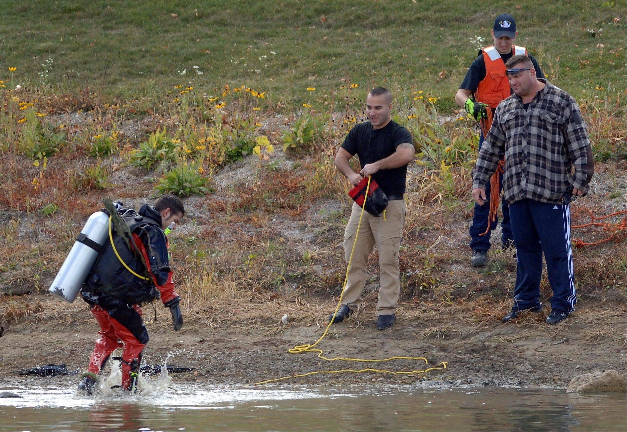 Fox Lake Fire Protection District diver Sam Santiago finishes a search of a pond in the Remington Pointe subdivision in Volo on Friday.