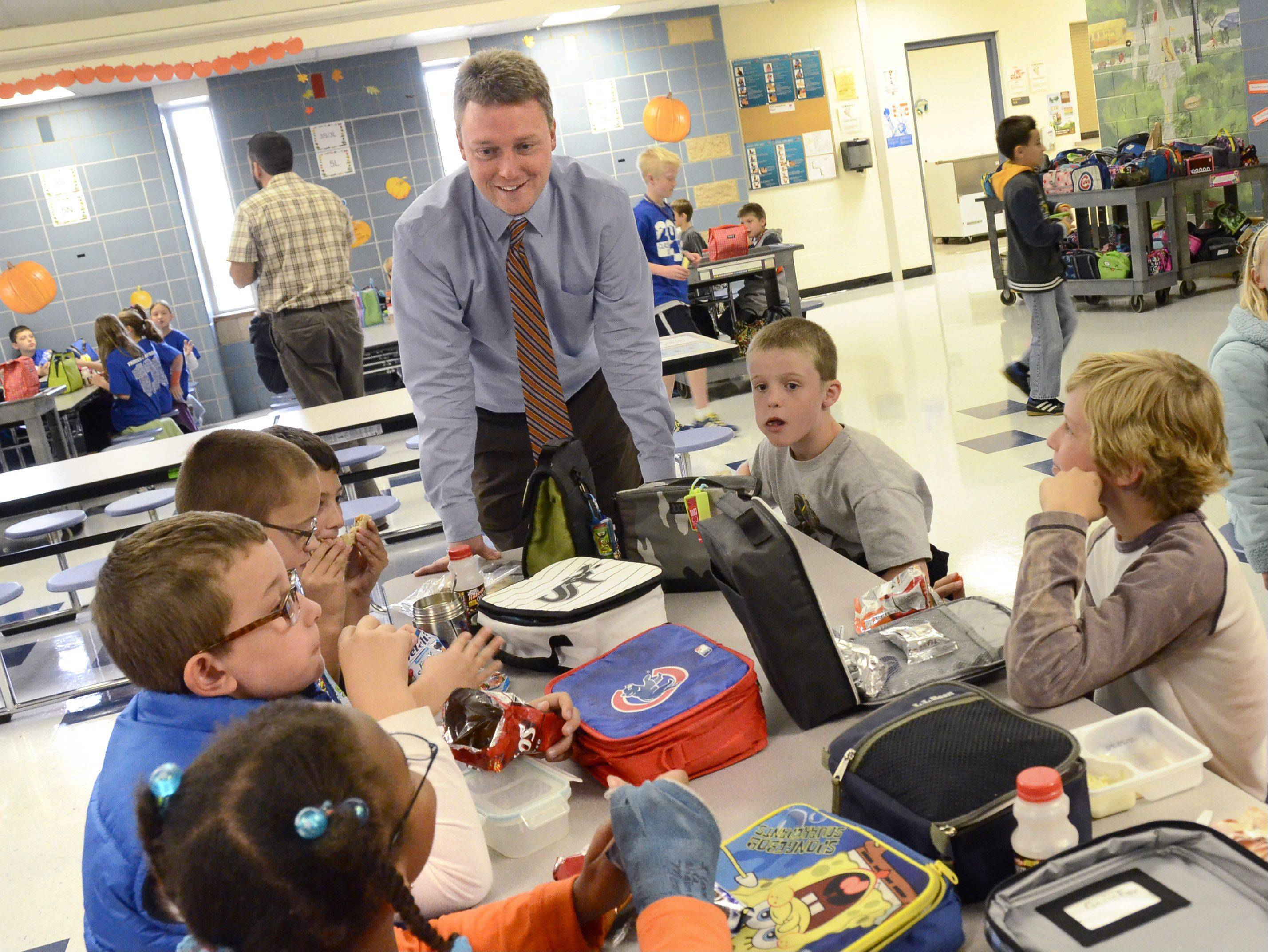 Dan Ophus, new principal at Fairview Elementary School in Mount Prospect, talks with students at lunch as part of his daily routine.