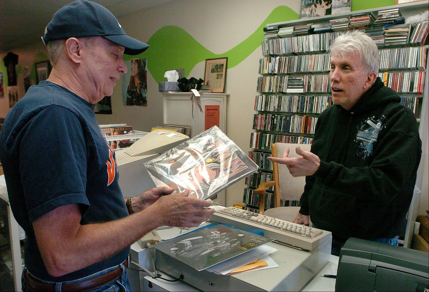 John Thominet visits with a customer in his Barrington record shop.