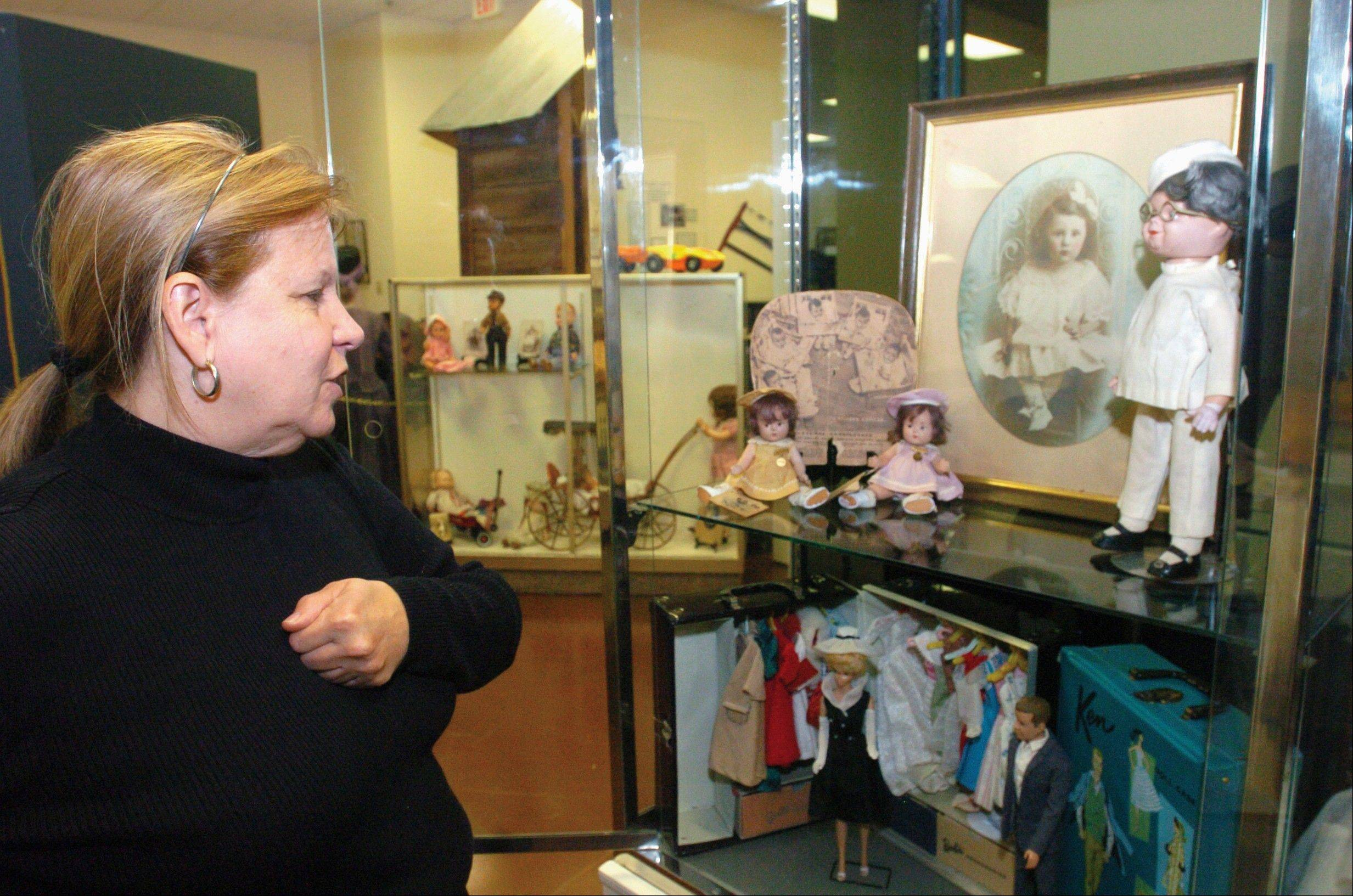 "Vermilion County Museum director Sue Ritcher talks about two of the Dionne Quintuplets dolls that they have on display at the museum as they get ready for the Arts Month Luncheon ""Tea for Two, Your Doll and You"" at the museum in Danville ."