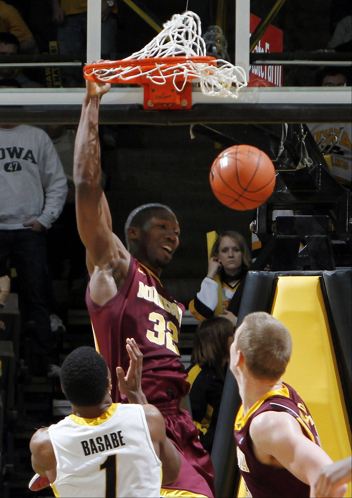 Minnesota's Trevor Mbakwe dunks over Iowa's Melsahn Basabe during a game Feb. 13, 2011, in Iowa City, Iowa.