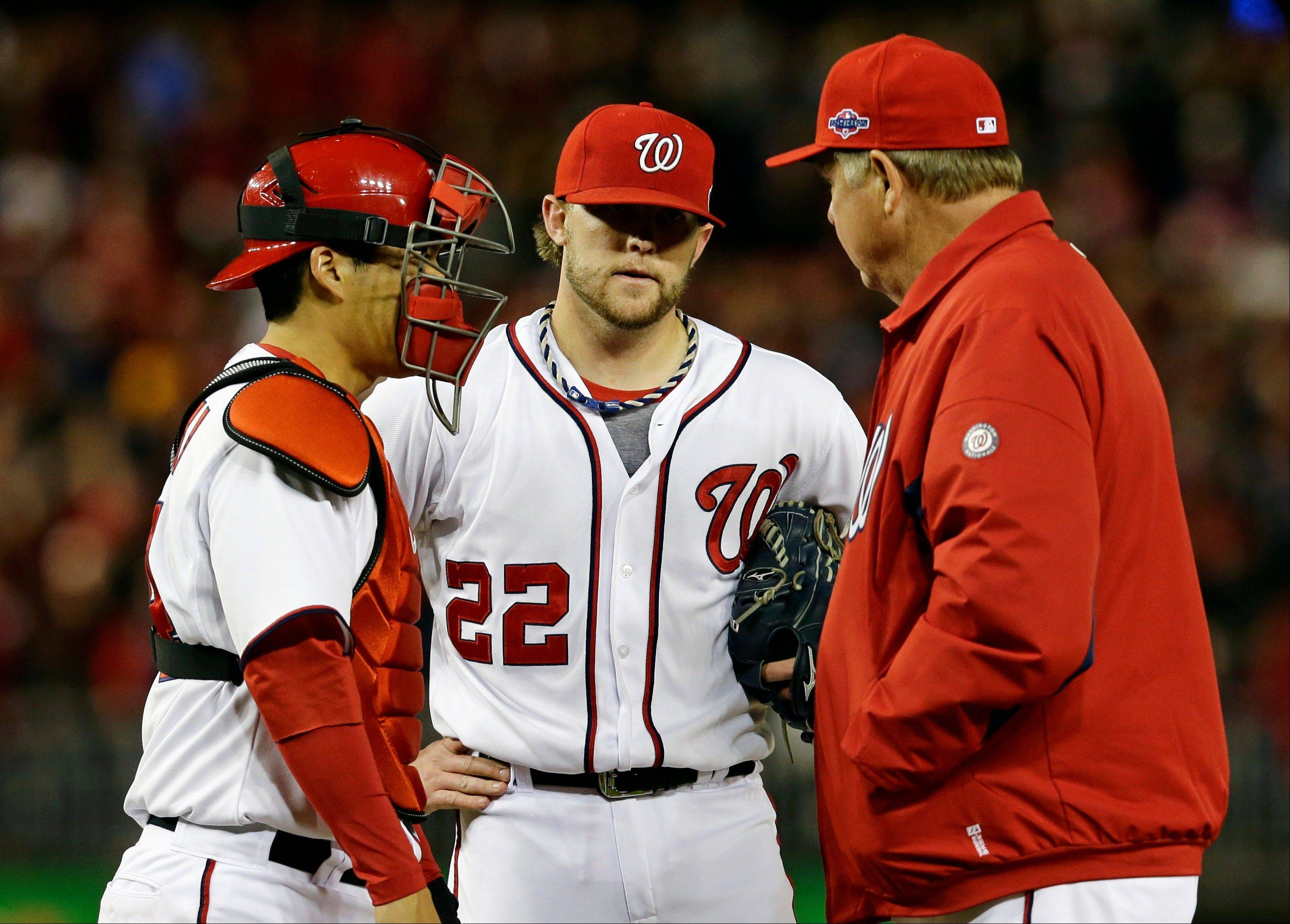 Washington Nationals relief pitcher Drew Storen speaks with catcher Kurt Suzuki, left, and pitching coach Steve McCatty in the ninth inning of Game 5. Storen twice had the Cardinals down to their last strike with two outs Friday night before giving up the lead.