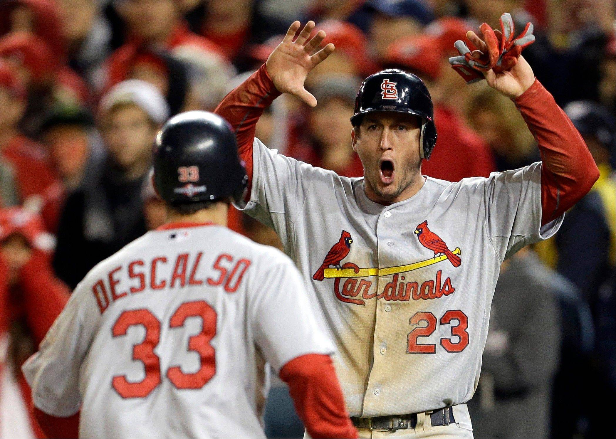 The Cardinals' David Freese, right, gives a yell as he and Daniel Descalso score on a single by Pete Kozma in the ninth inning of Game 5 of the National League division series in Washington.