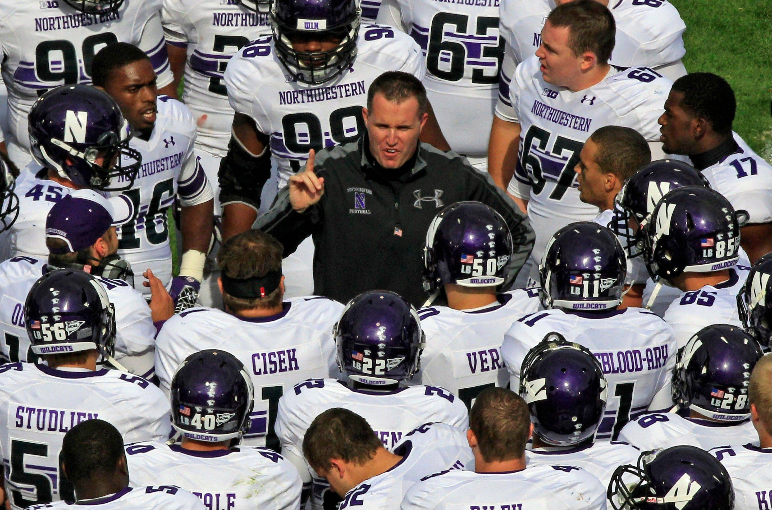 Northwestern head coach Pat Fitzgerald, center, talks to his team during the fourth quarter of Saturday's loss to Penn State. The NU spread offense, which averaged less than 4 yards per pass last week, will try to regroup against 4-1 Minnesota.