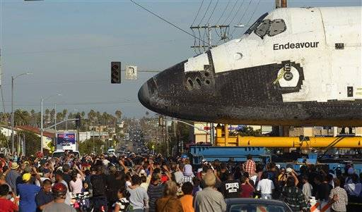 The space shuttle Endeavour is slowly moved down Crenshaw Blvd. at Slauson Ave., Saturday in Los Angeles. The shuttle is on its last mission — a 12-mile creep through city streets. It will move past an eclectic mix of strip malls, mom-and-pop shops, tidy lawns and faded apartment buildings. Its final destination: California Science Center in South Los Angeles where it will be put on display.